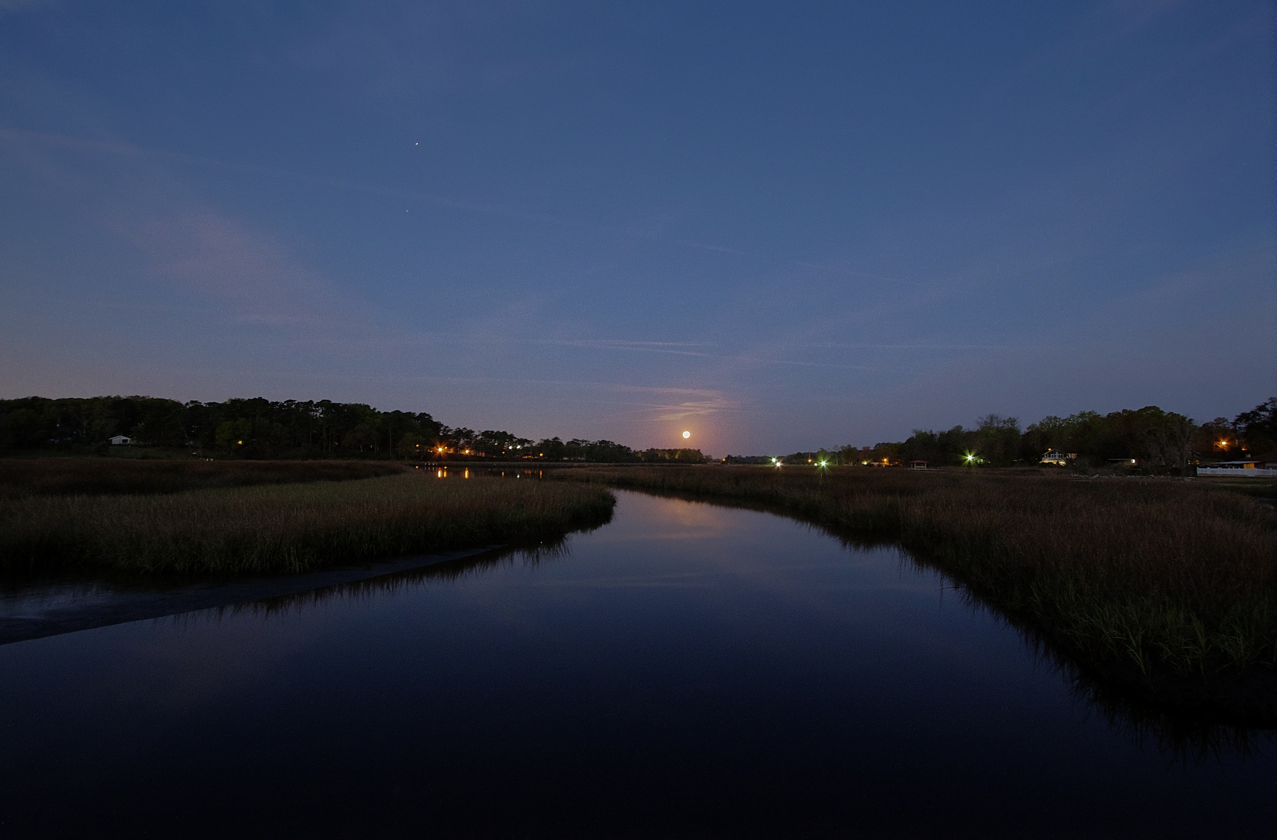 The setting full moon pulls the curtain of night below the western horizon.
