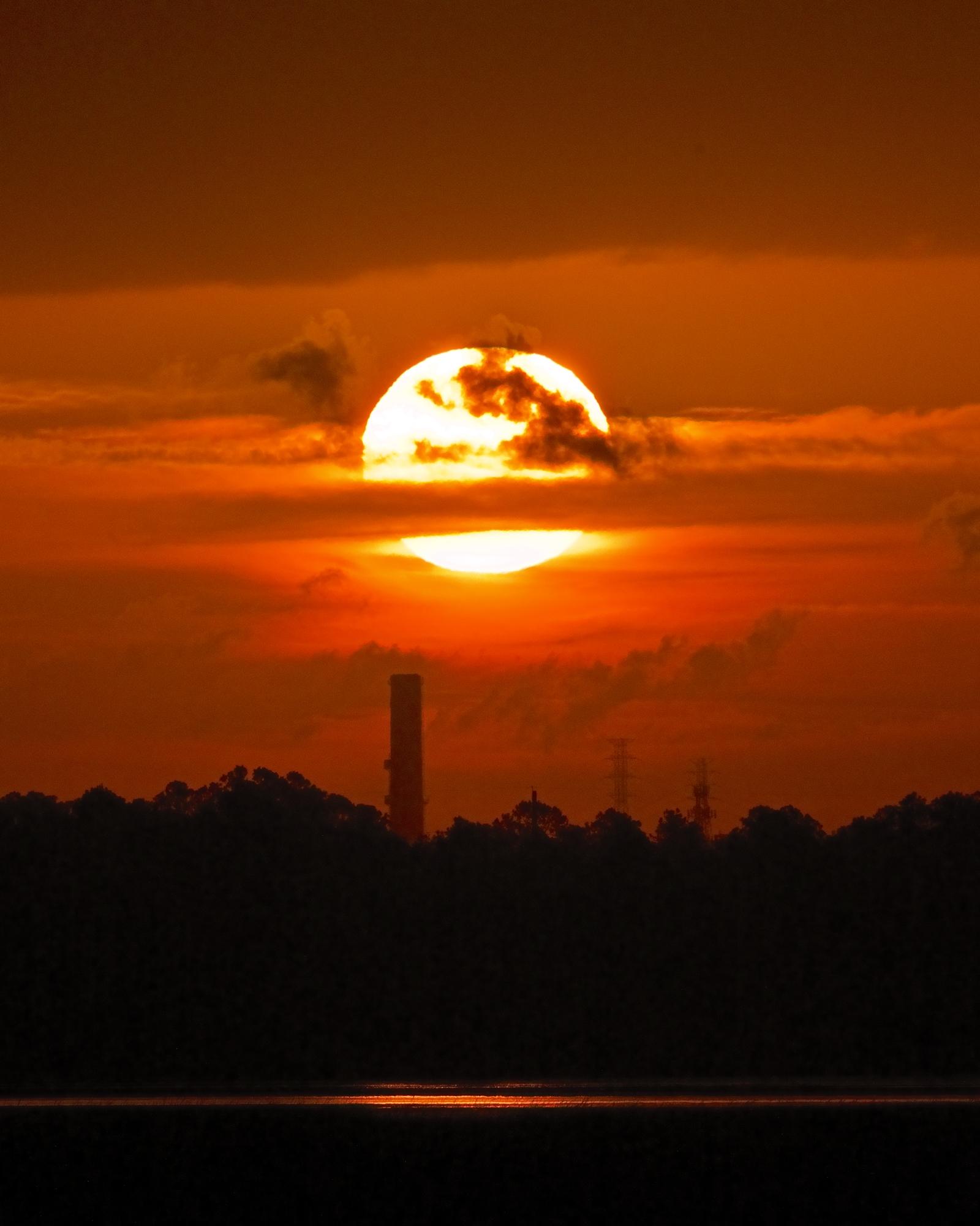 The sun burns through a layer of clouds like a molten fireball.