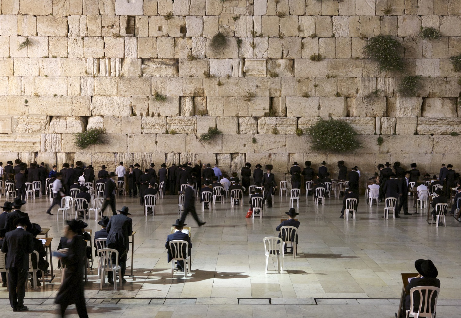 Jewish men pray, chant, and sway in front of the Western Wall, also called the Wailing Wall, located in the Old City of Jerusalem. This shrine, the last remnant of the Temple Mount destroyed by the Romans in 70 CE, is considered Judaism's holiest prayer site.
