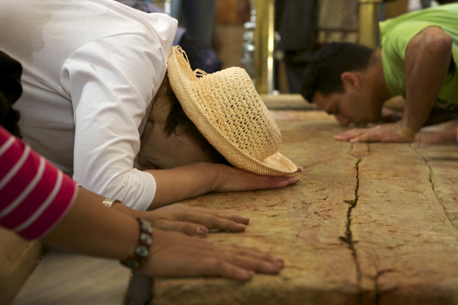 Visitors kiss and touch Jerusalem's large slab of holy stone at the Church of the Holy Sepulchre, also called the Basilica of the Holy Sepulchre, in the Christian Quarter of the walled Old City. The Church, which is considered the most important shrine in the Christian world, is believed to have been built over the site where Christ was crucified, buried, and resurrected.