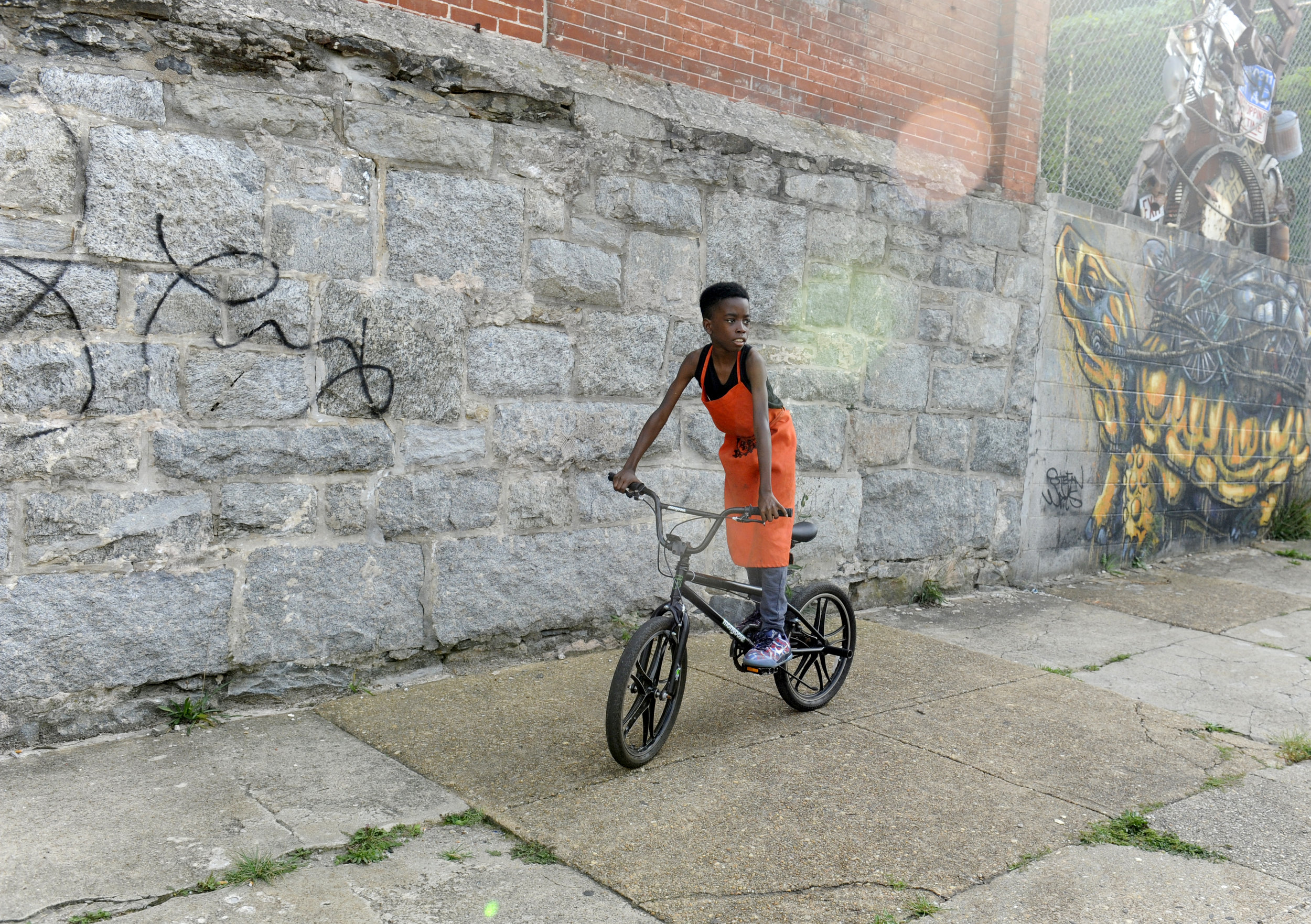 Tisean Muhummad, 12, rides outside BYKE headquarters on E Oliver Street in Baltimore, Maryland on Thursday, September 8, 2016. The Baltimore Youth Kinetic Energy Collective (BYKE) is a youth empowerment after-school program.