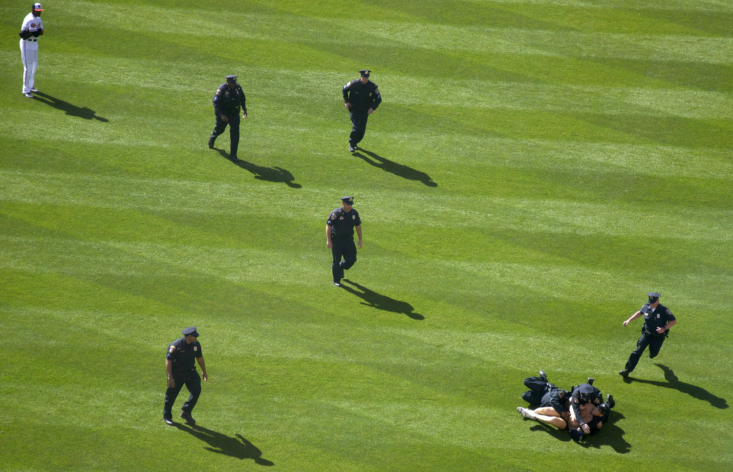 Mark Harvey of Severn, Maryland, is pinned down by police after running across the Camden Yards field during the Baltimore Orioles Opening Day on April 6, 2012.