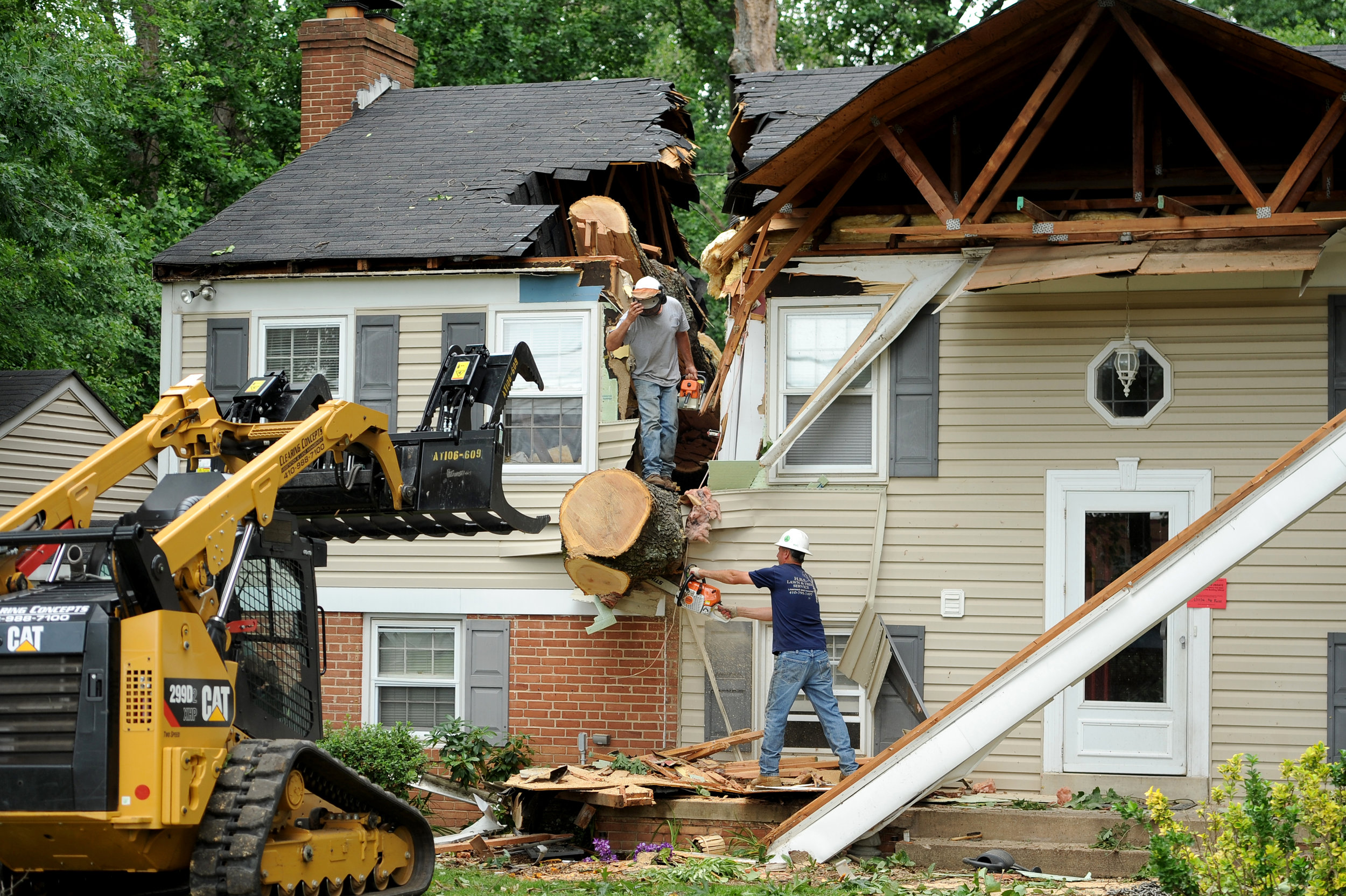 A crew helps clear a tree that fell on a house in Glenelg, Maryland on Wednesday, June 22, 2016, after a tornado touched down in Howard County Tuesday afternoon.