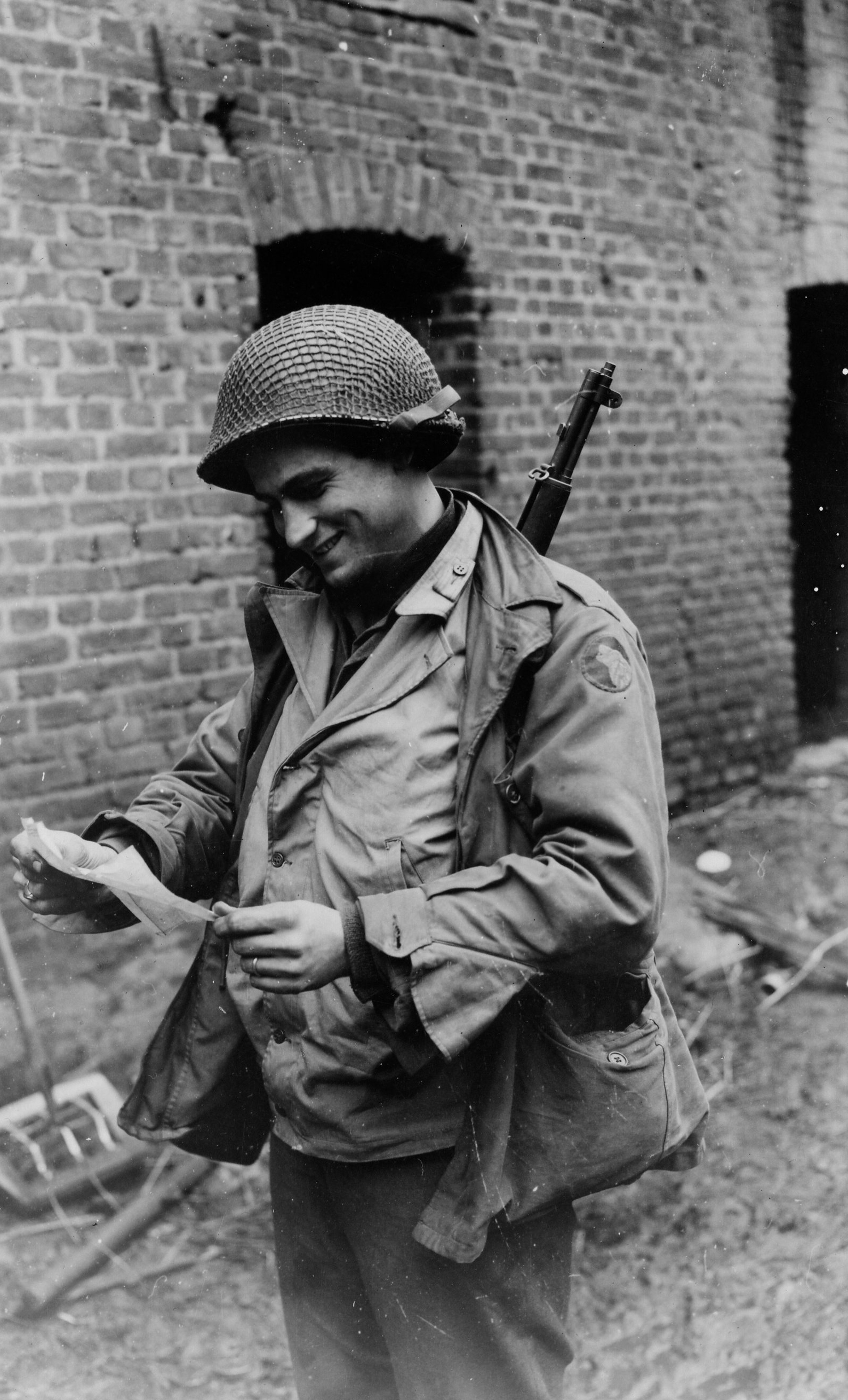 Dec 1944. GI from Long Island, NY reads cable announcing the birth of his son in November.