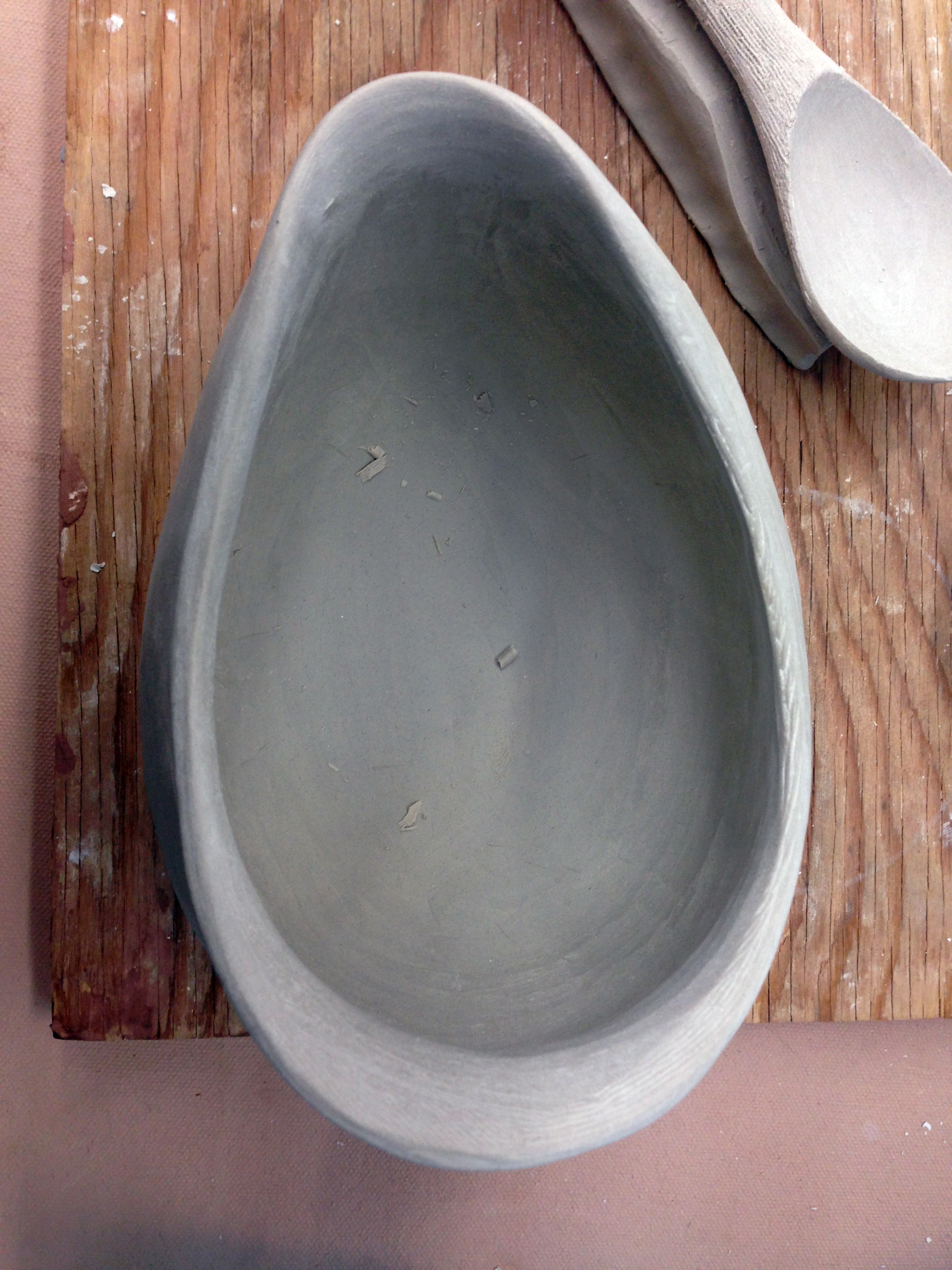 Considering a curved spout design for a feeding vessel, so that someone can offer liquid to another who is sitting to her left.