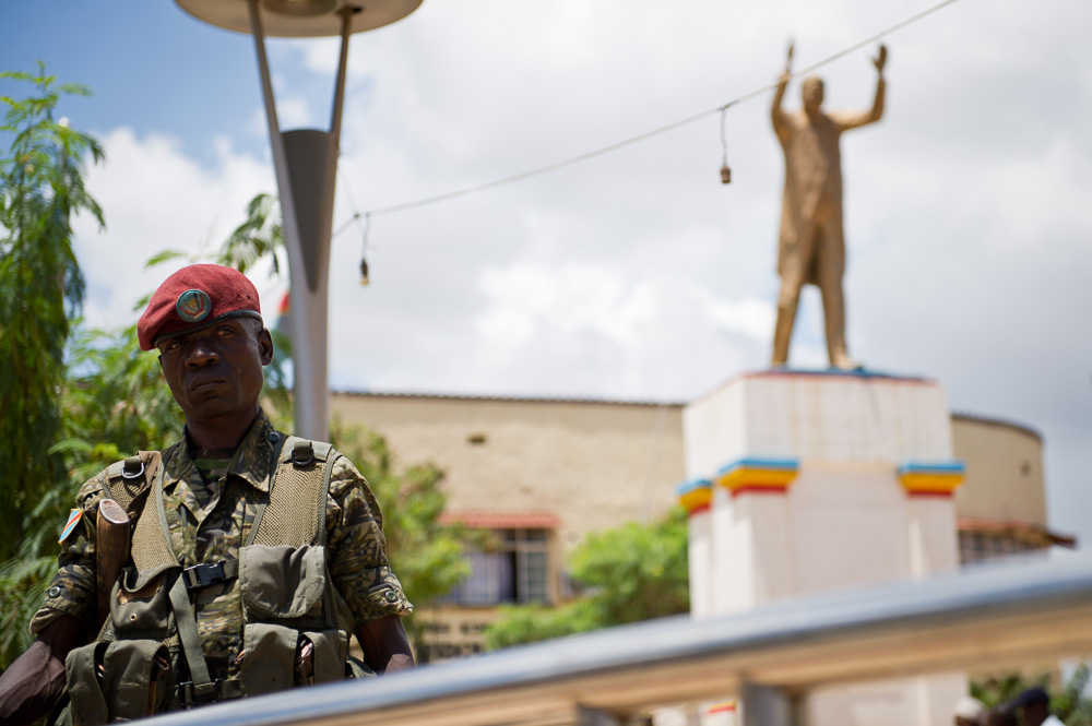 A soldier stands below the statue of Moise Tshombe