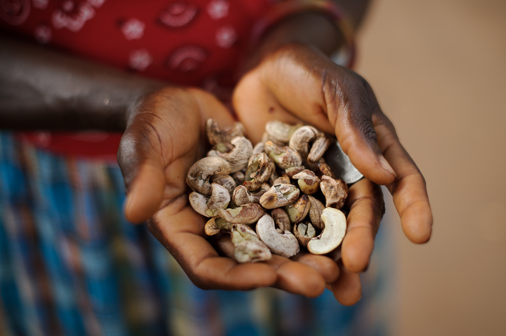 A lady holds $1 (USD) worth of cashew nuts, for sale in the streets of Bissau
