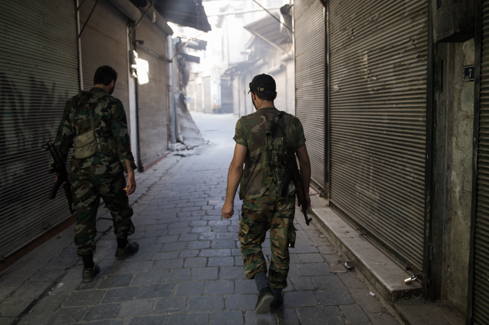 FSA fighters walk through a closed market in the Old City. August 2012.