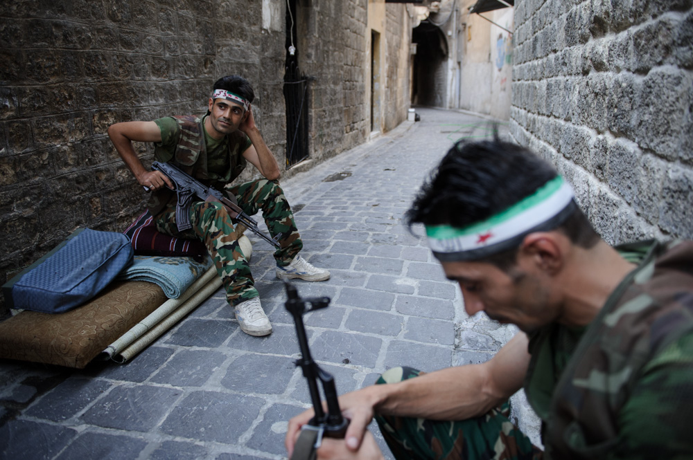 Rebel fighters sit in a lane of the Old City. August 2012.