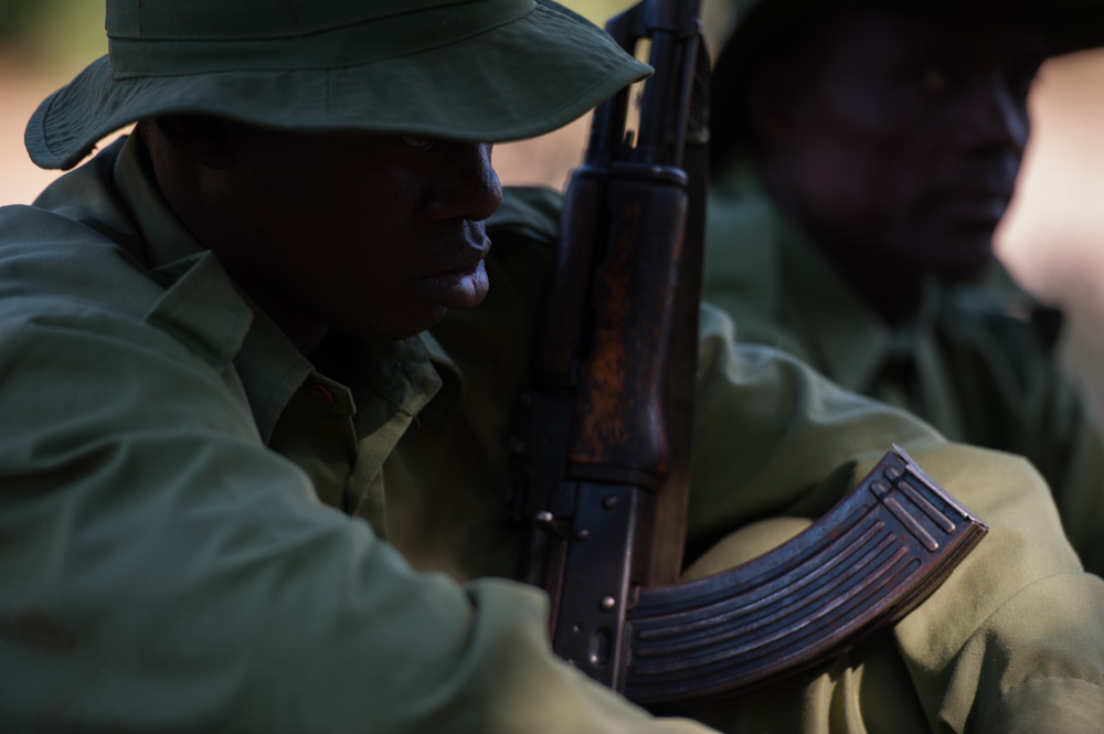 Wildlife rangers sit whilst out on patrol in Selous