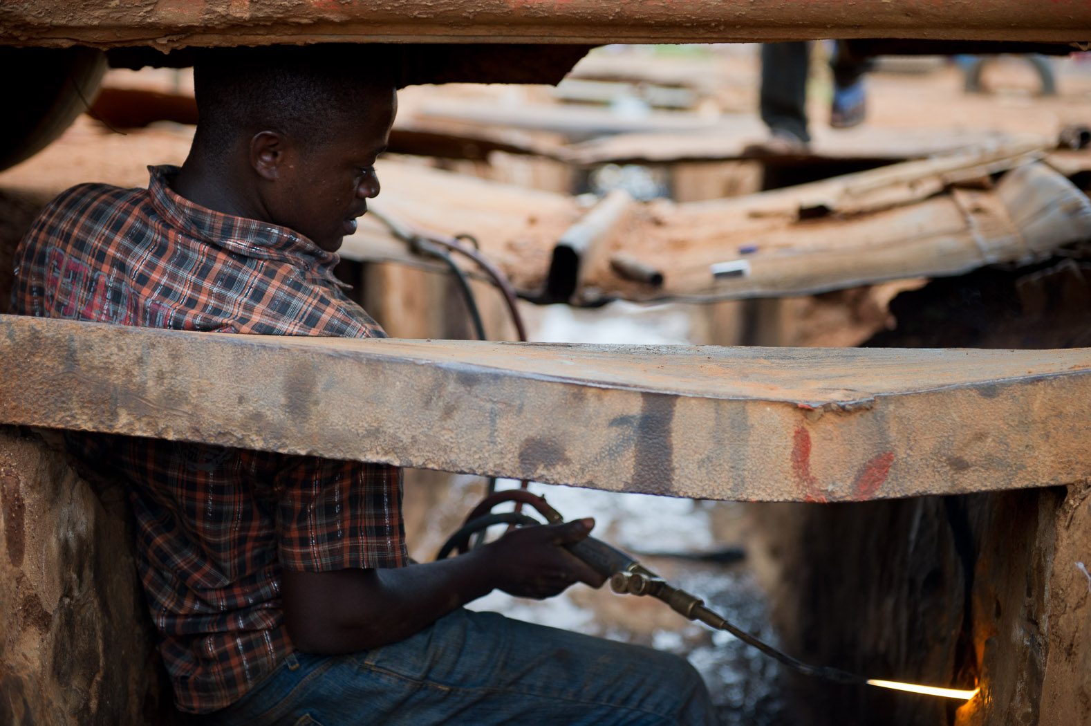 A man uses a drainage canal to work on a minibus. The Congo has some of the lowest development indicators in the world.