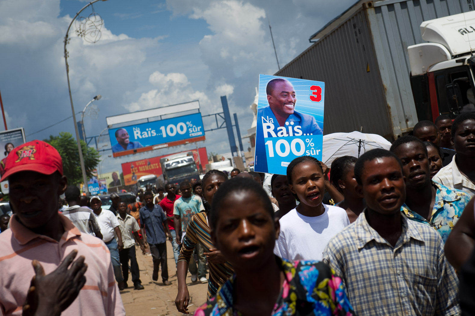 "Supporters of incumbent President Kabila march through the centre of Lubumbashi, carrying posters with his campaign slogan of ""Na Raïs, 100% sûr"" ('With the President, 100% sure') on the final day of campaigning."