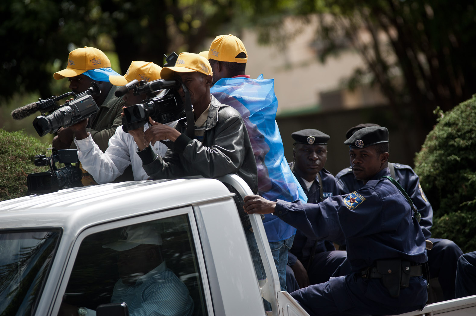 Cameramen, all wearing campaign material for President Joseph Kabila and accompanied by police, film a pro-Kabila candidate on the final day of campaigning.