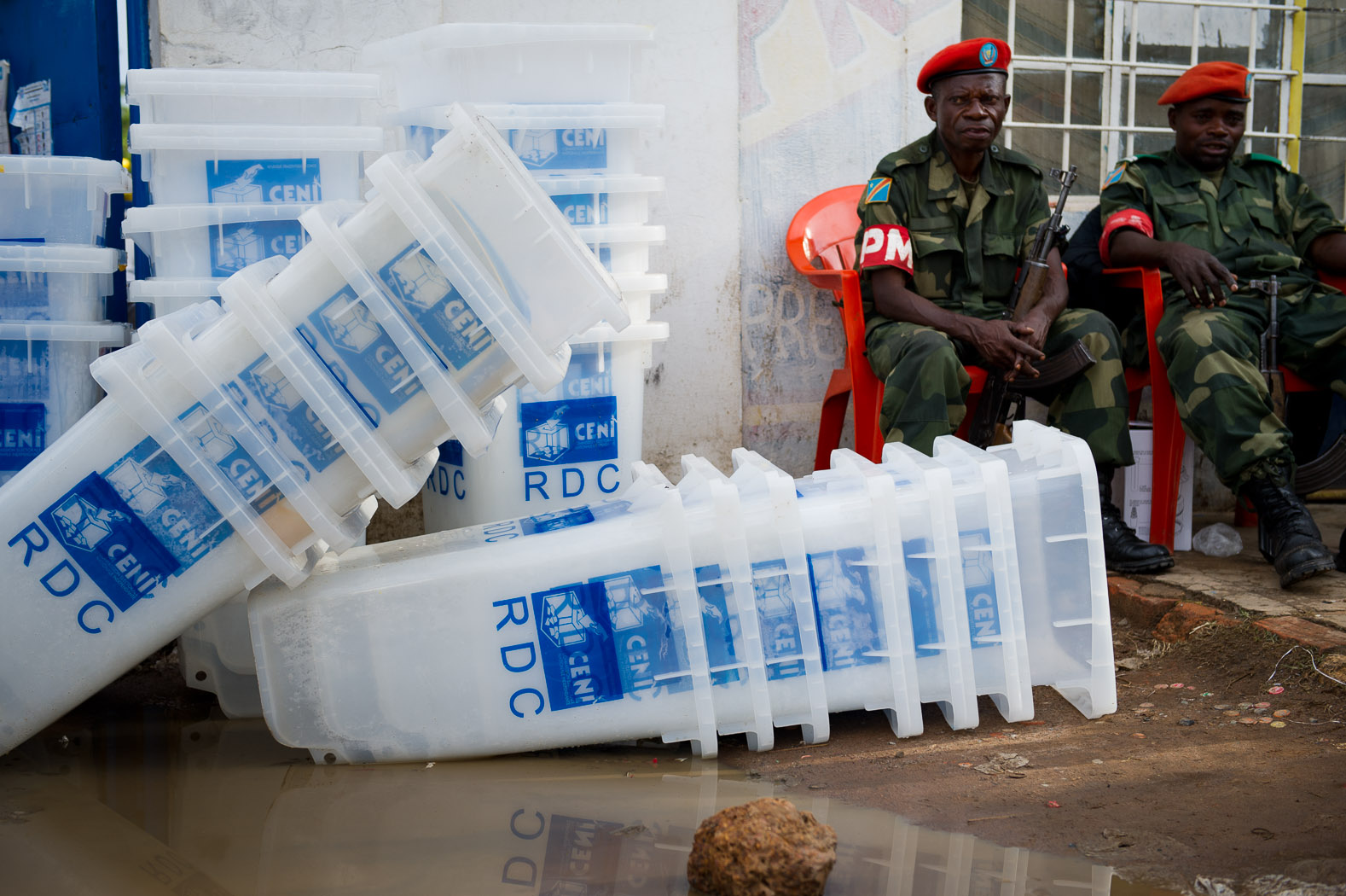 Armed Republican Guard soldiers sit outside the Independent National Electoral Commission (CENI) offices in Lubumbashi as bags of cast ballots arrive. The army and police were on high alert after attacks in the city, and expected further aggression against the CENI.