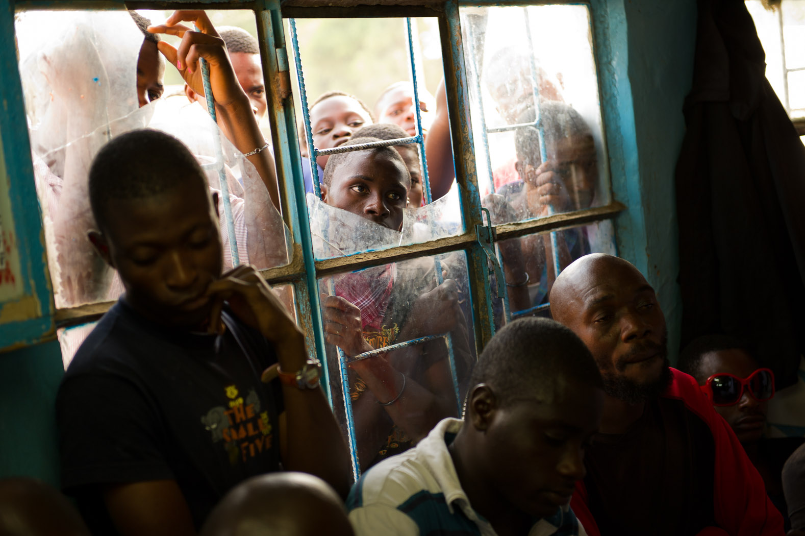 In a district of Lubumbashi largely populated with opposition supporters, men peer through the window of a barbershop to watch the results.