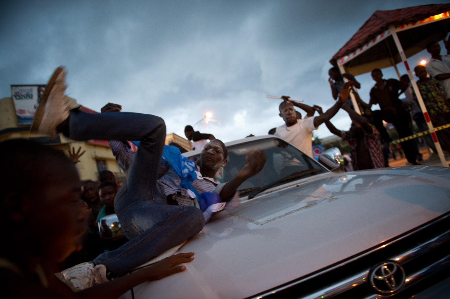 A supporter of incumbent President Joseph Kabila rolls over a car as he celebrates Mr. Kabila's win.