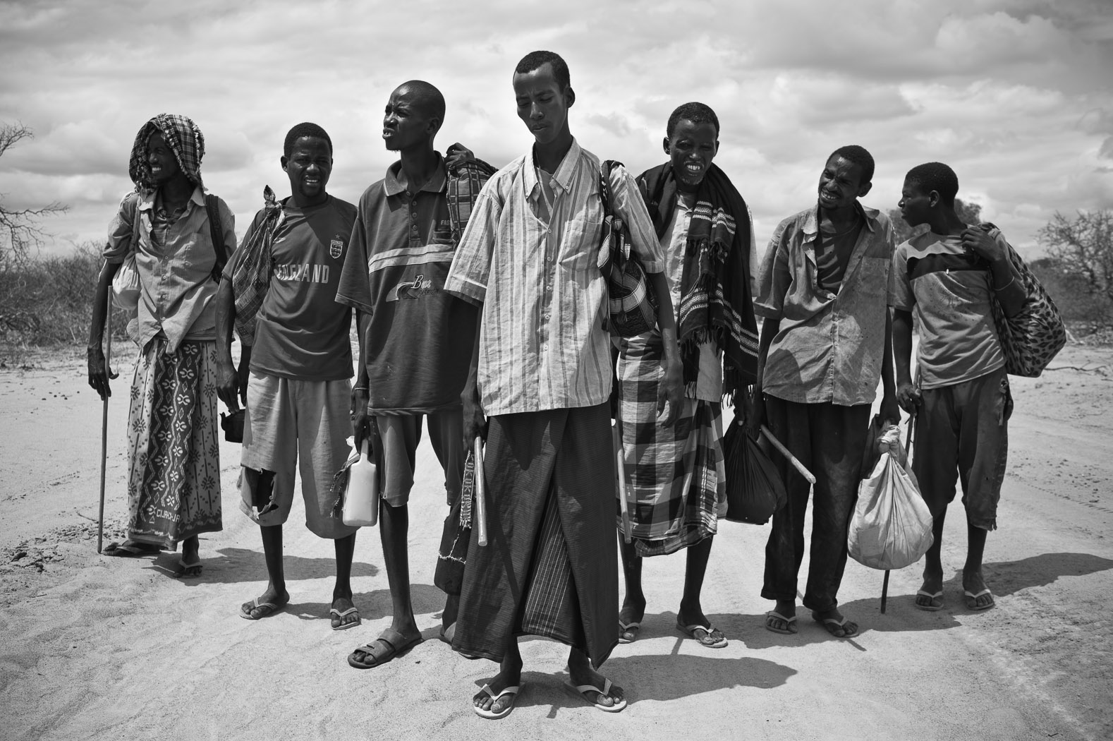 This group of seven men left their home in Dinsour, Somalia, fifteen days previously, and are walking to Kenya's Dadaab refugee complex. Their families have already made the journey, and they are hoping to be reunited with them, in one of the three camps that now house over 380,000 people. Here, they stand on the sand-road for this photograph, just half an hour after having crossed the Kenyan border, with still around 100km to walk before Dadaab.