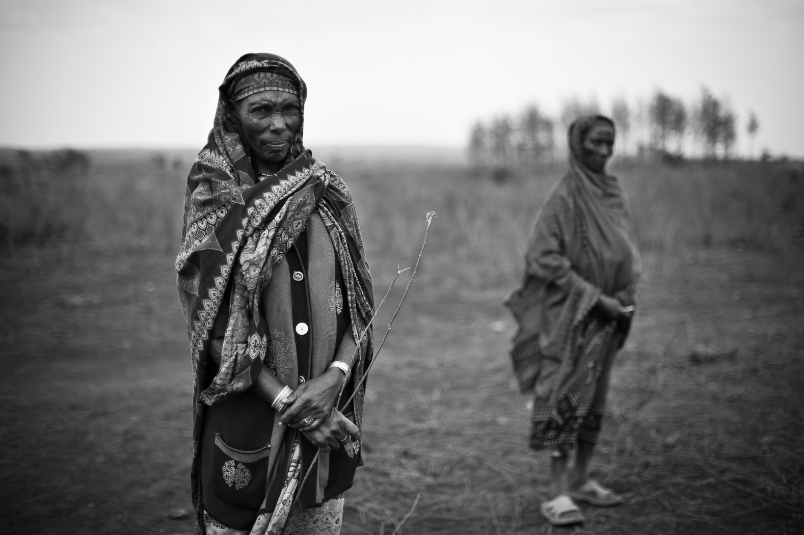 """The Marsabit region used to be known as the bread-basket of Kenya; as little as twenty years ago, there used to be large areas of forest here, and plentiful rain. The landscape today is arid scrubland, where animals now compete with humans for any available water, which is having to be trucked in from distant water sources.  Helema Guy (left) and Kula Roba (right) have lost almost all of their livestock through the drought. Living close to Marsabit, they say that the rains have failed here for several years.  Helema will sell one of her few remaining goats, today, to an NGO """"livestock off take"""" programme, where they will receive money for the animal, as well as the meat, to share amongst two other households."""