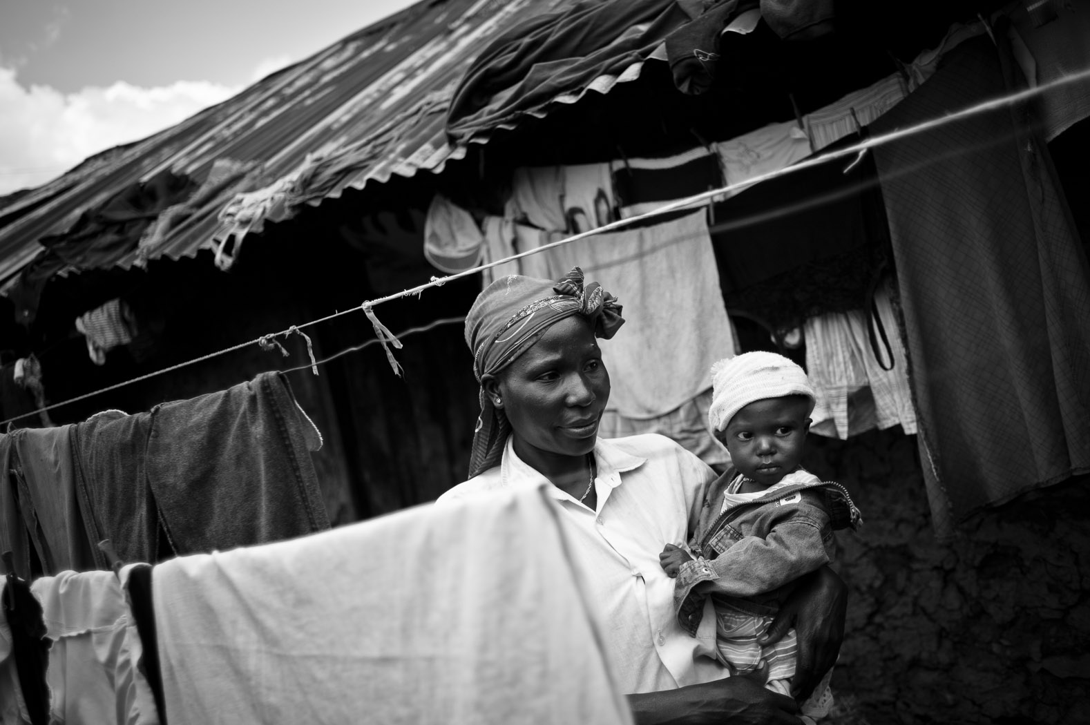 """In the Korogocho slum of Nairobi, Kenya, another side of the drought can be seen. Whilst food is available in the markets here, the huge impact that failed rains have had on the price of food, exacerbated by a global and regional fuel crisis, has pushed many families to the brink.  Rosemary Auma and her daughter, Millicent Mukundi, stand in the yard of their home in the slums. Millicent is suffering from malnutrition; Rosemary says that with only casual work for her and her husband, it is difficult for her family to have more than one meal a day.  """"Life is much harder in the city, if there is no work you won't eat"""", she says."""