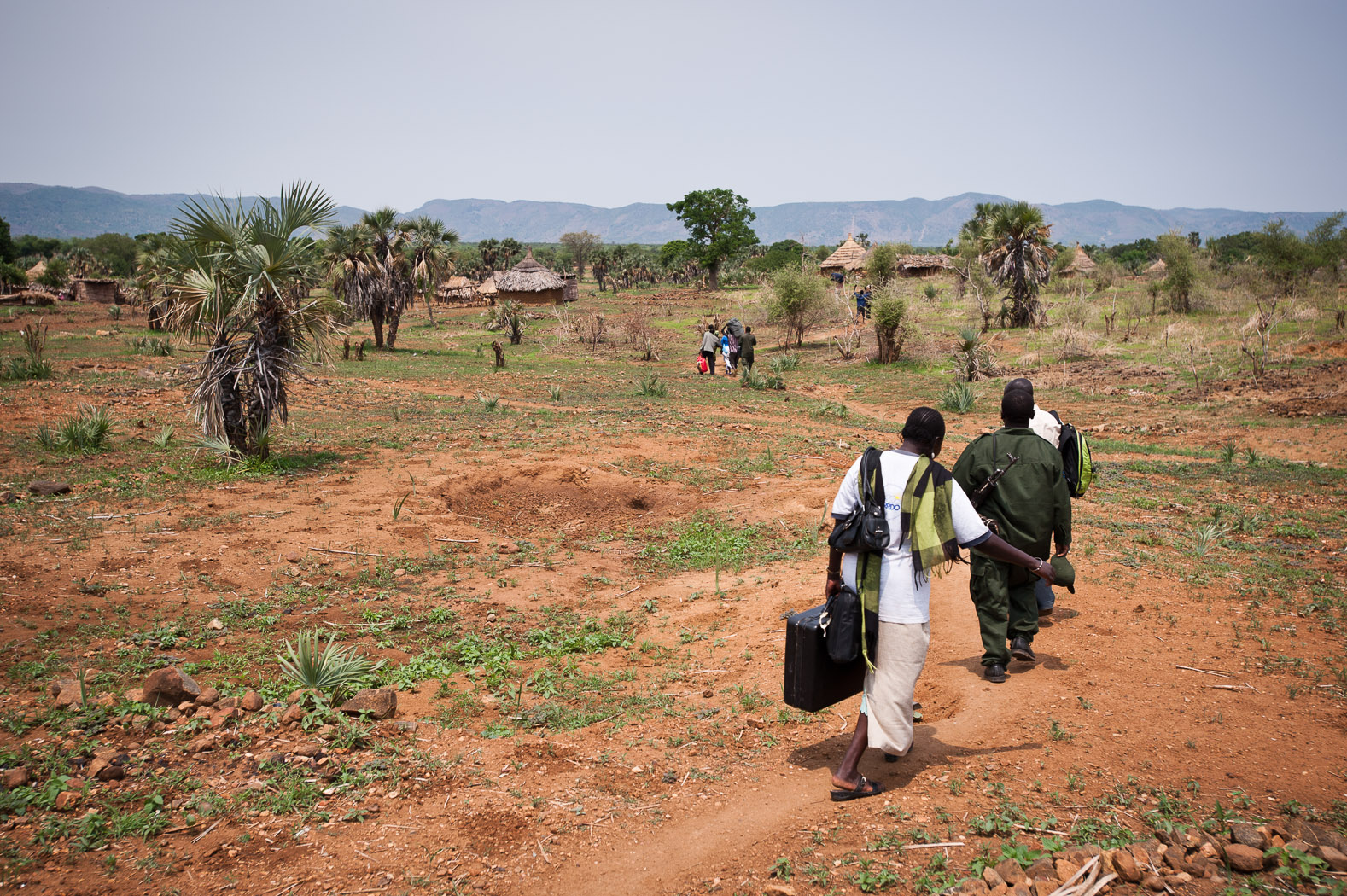 Many of the Nuba, however, have fled their homes and the region. Here, a group of Nuba walk across scrubland south-east of Kadugli with a few belongings packed into suitcases, hoping to find a way out of South Kordofan.