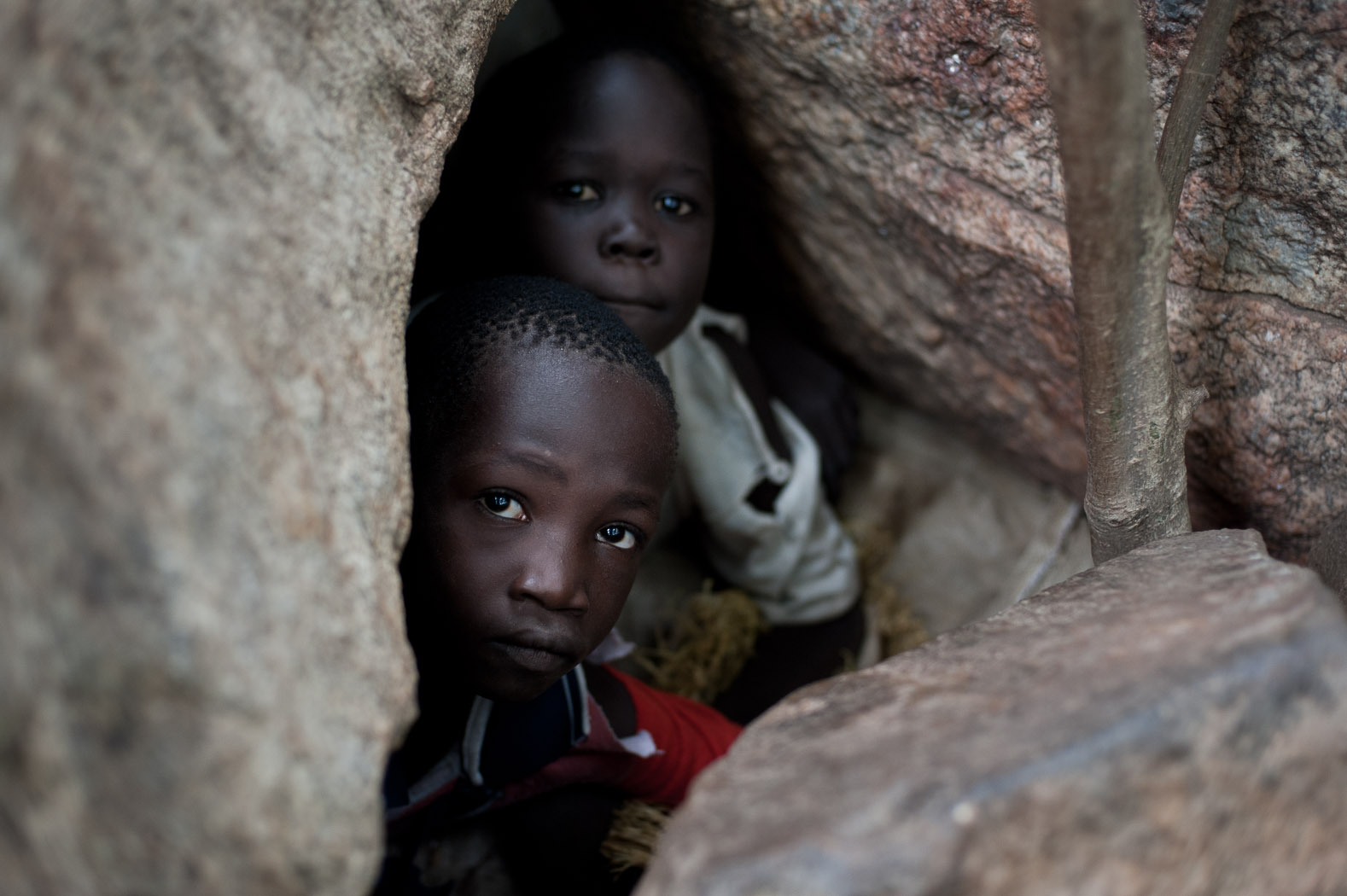 """A group of children peer from a cave in a dried river bed as they take shelter from aerial bombardments. As well of the threat of the aircraft, they also fear snakes and other animals living in the caves. """"We saw a snake go in once, but when a plane flew we had to take cover"""" said one child. """"We never saw the snake come out again."""""""