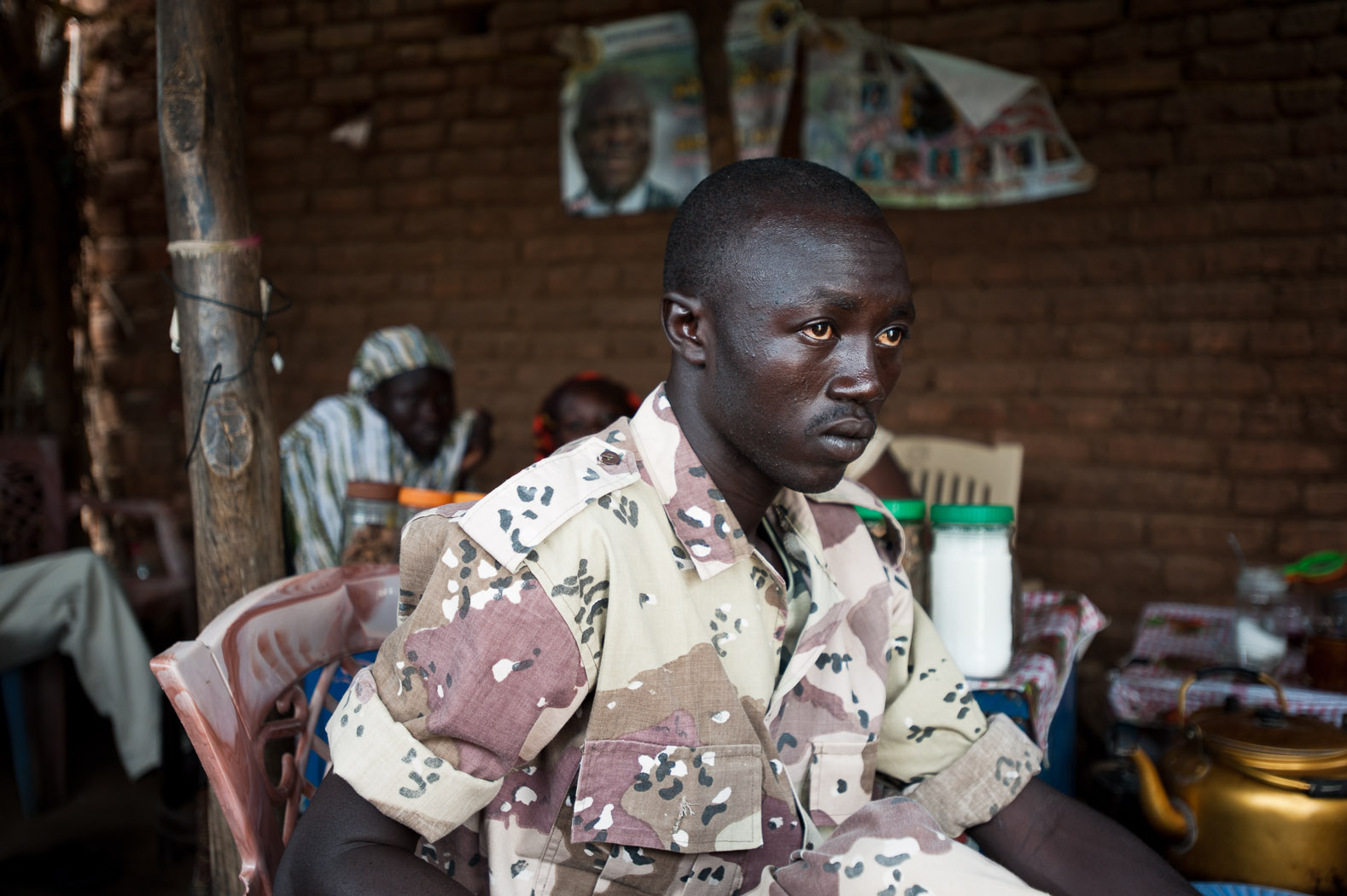 """Cola Kuku Codi, a former SPLM-North fighter, sits in a coffee-house in Kauda, the base of the SPLM-N in South Kordofan. He is no longer fighting, but staying to protect his village. But he is prepared to go back to fight. """"Now I am ready if they want to take me on a mission"""" he says, adding """"I don't think peace will happen again with these people [the Khartoum government]."""""""