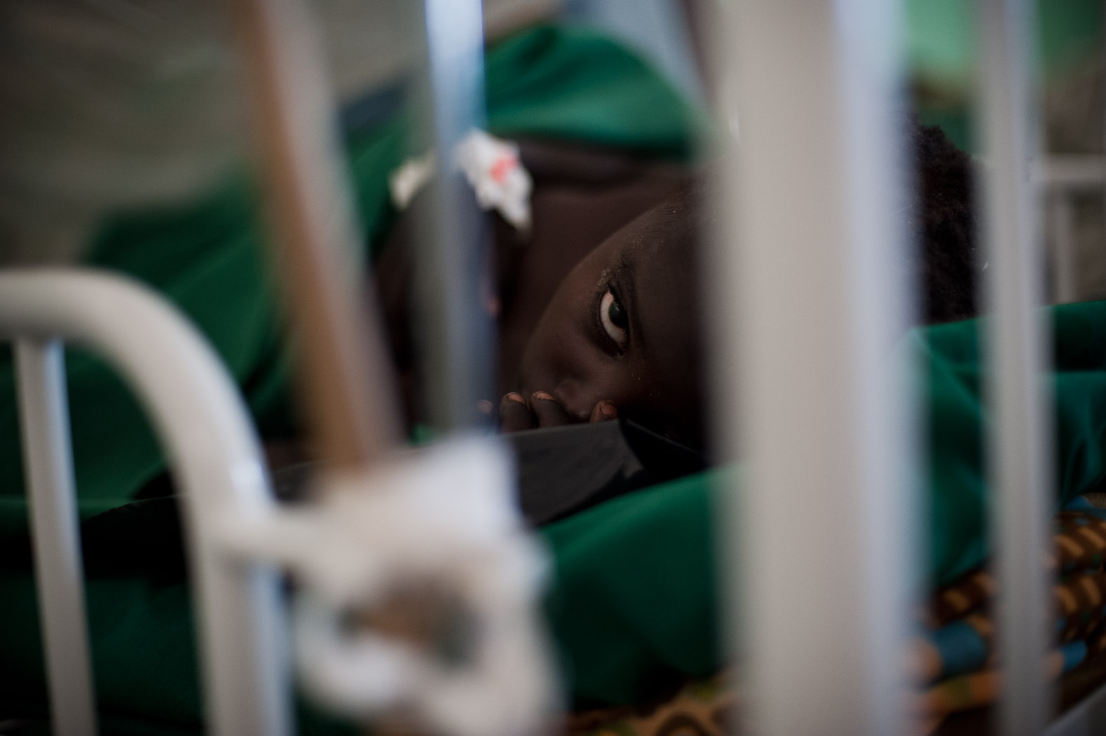 """Viviana Issa lies paralysed in a bed at a medical facility in Sudan's Nuba mountains. """"I don't know what to do with this girl"""" says the only doctor in this facility. Viviana is leaking spinal fluid, and paralysed from the chest down after her spinal cord was severed by a bomb fragment hit her in the neck, breaking vertebrae. The bombing also killed two of her siblings."""