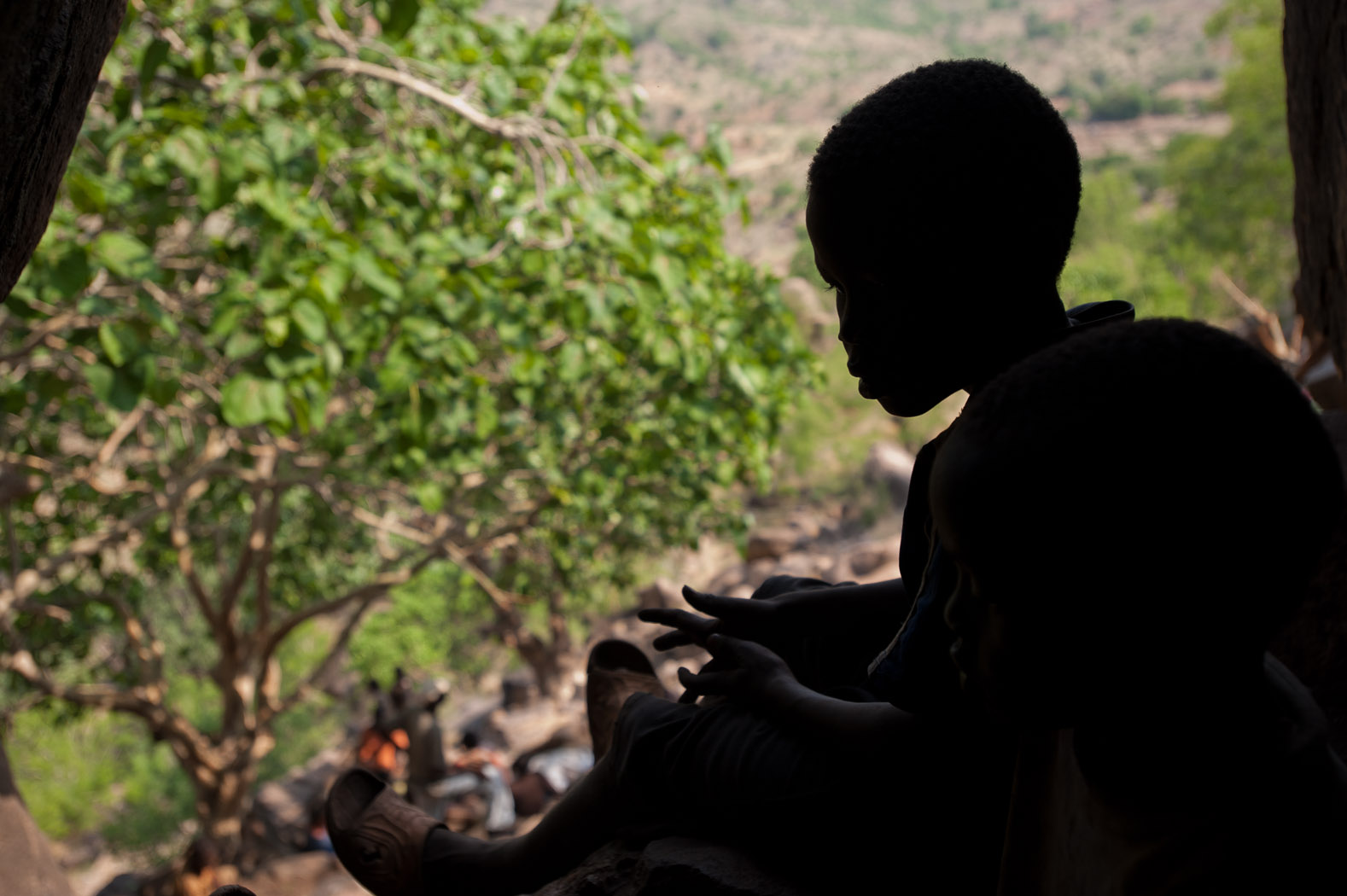 A child spends his afternoon in a cave in the Nuba mountains, as his family and fellow villagers shelter from the risk of bombs in the region.