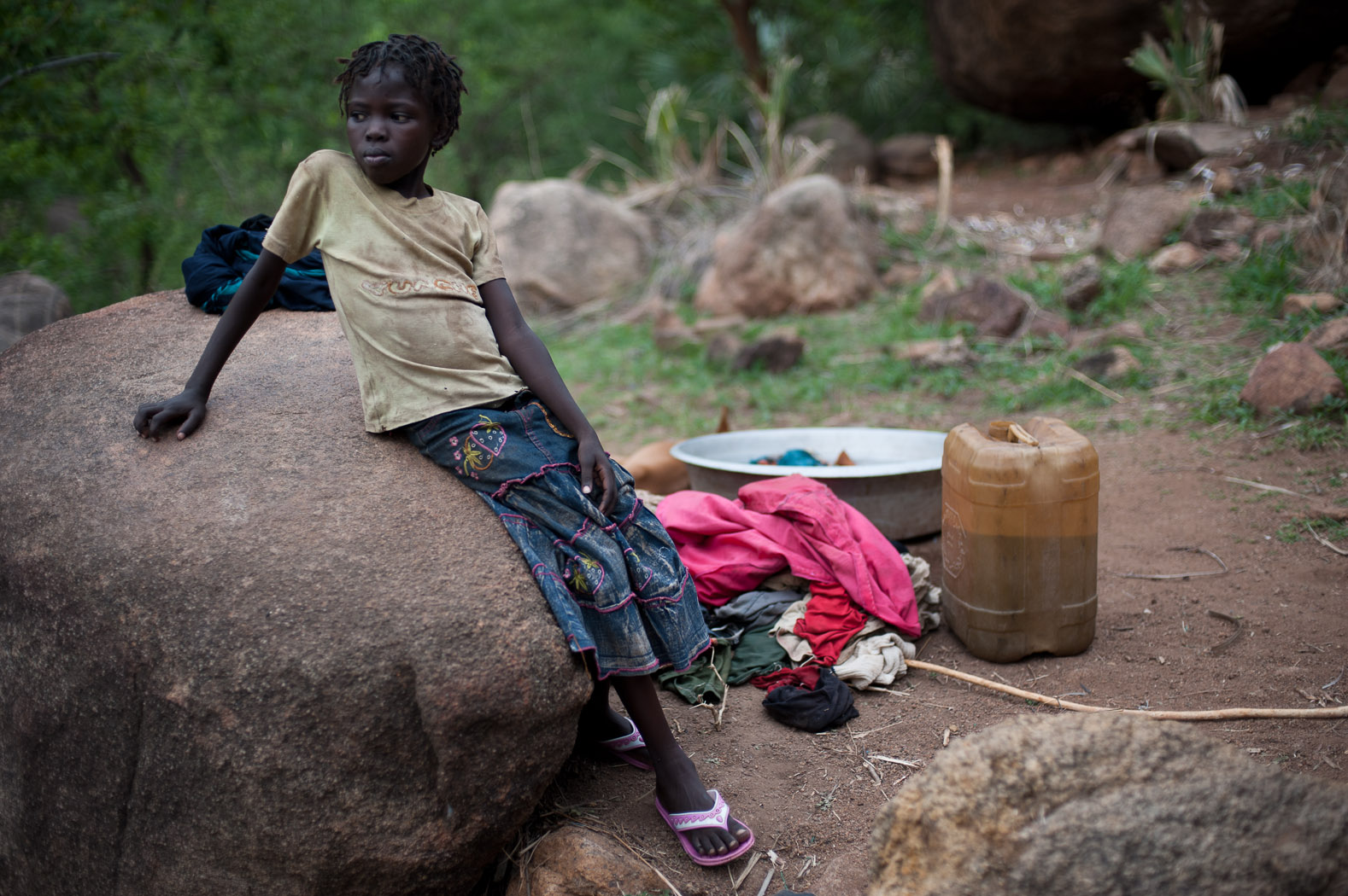 A girl stands next to her family's washing near a cave in the Nuba mountains. Life has taken an almost everyday quality in the hills above Kurchi, as the families taking refuge here continue their daily chores amongst the rocks.