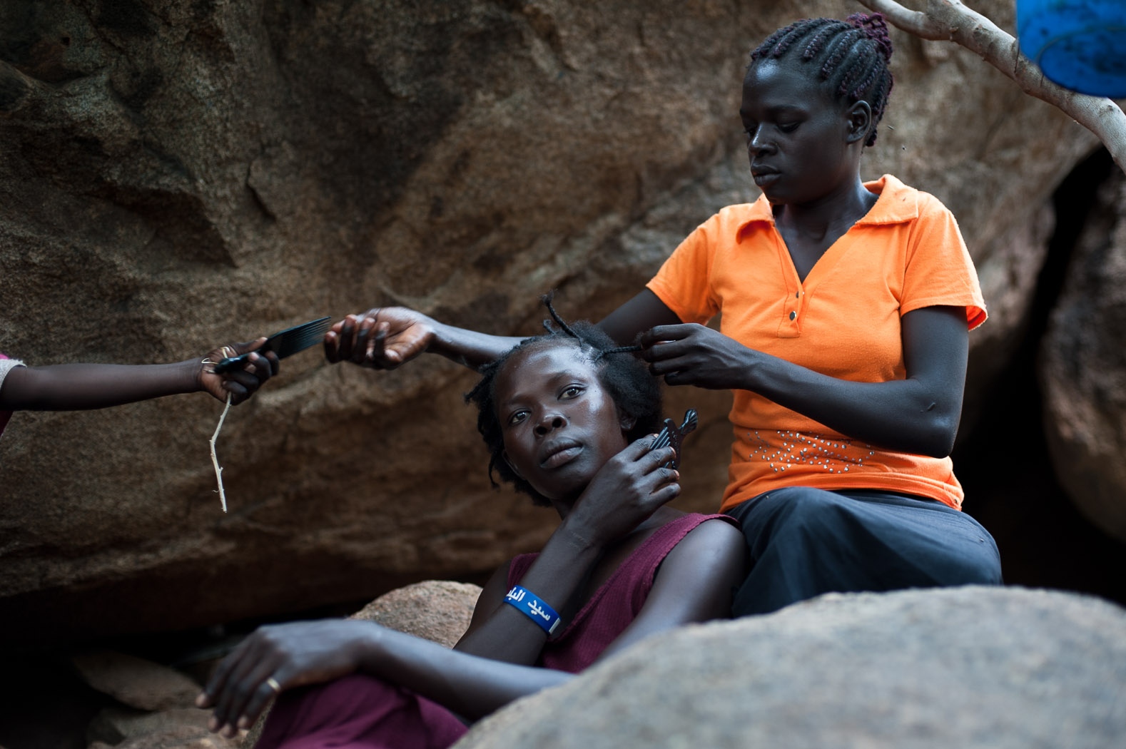 Unable to work their fields, a group of women braid their hair during the monotony of days on the hillside above Kurchi.