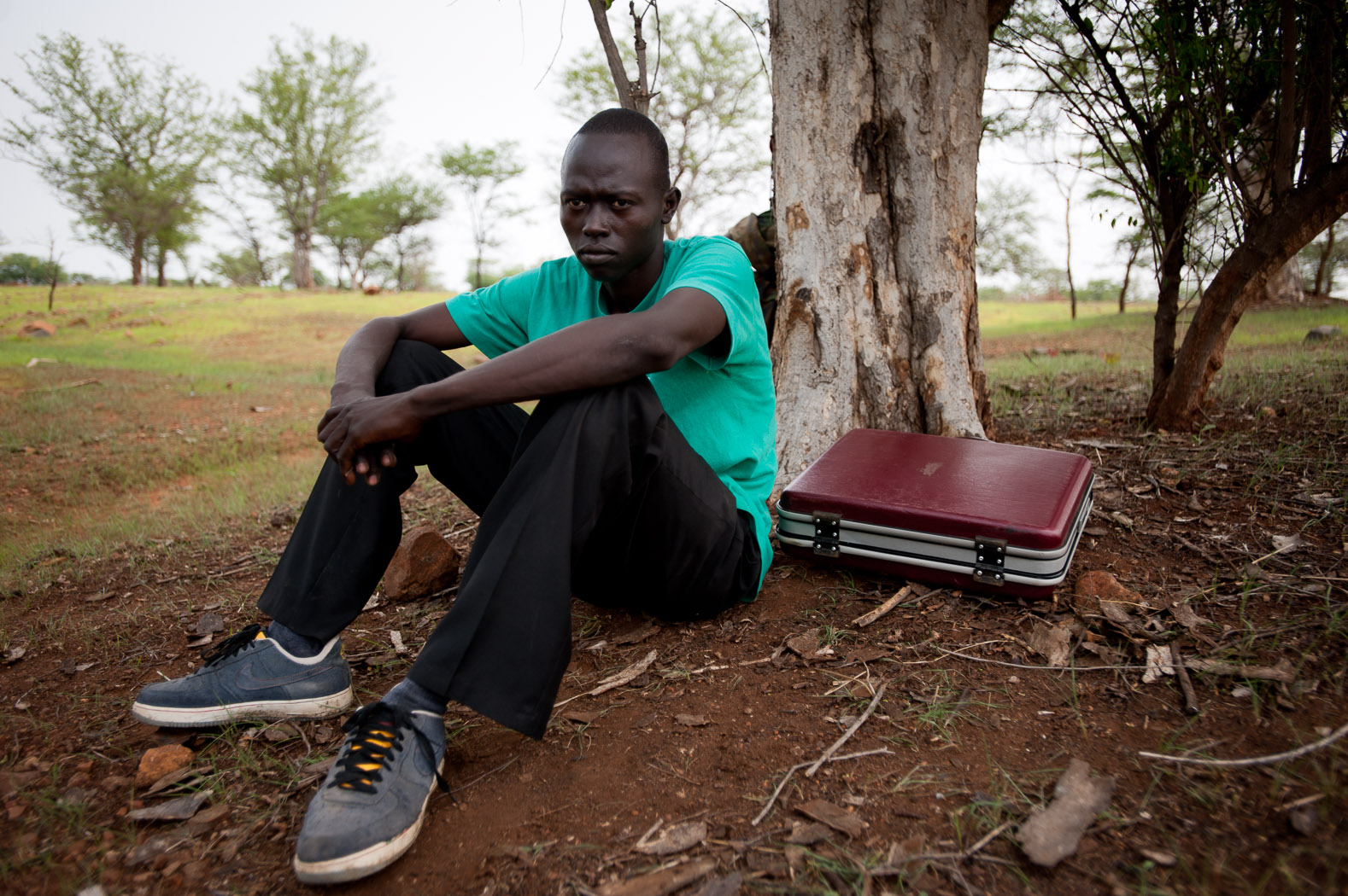 """For others, though, they just hope to leave. Joseph from Kauda says """"I hope to get to Kenya, to take refuge ... for the sake of security - I don't feel secure here"""".  Joseph left Kauda two days ago, and sitting with his only possessions is taking shelter, hiding under a tree as Anotonov bombers drone overhead."""