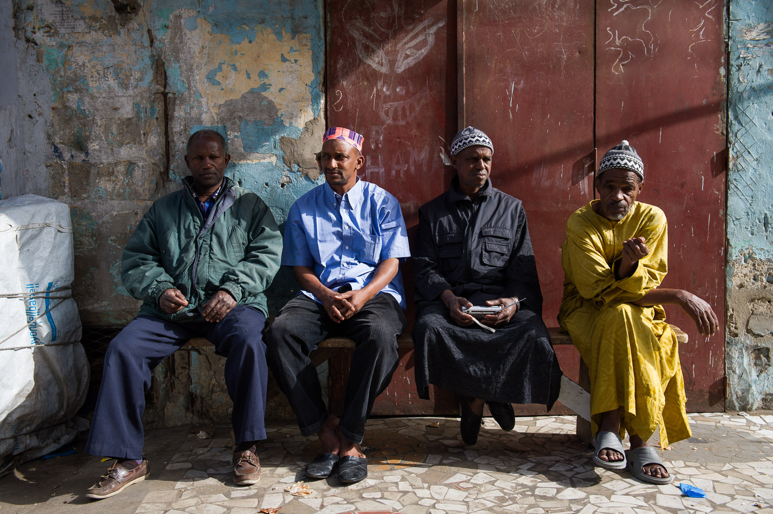 Men sit outside a polling station in the capital's centre.