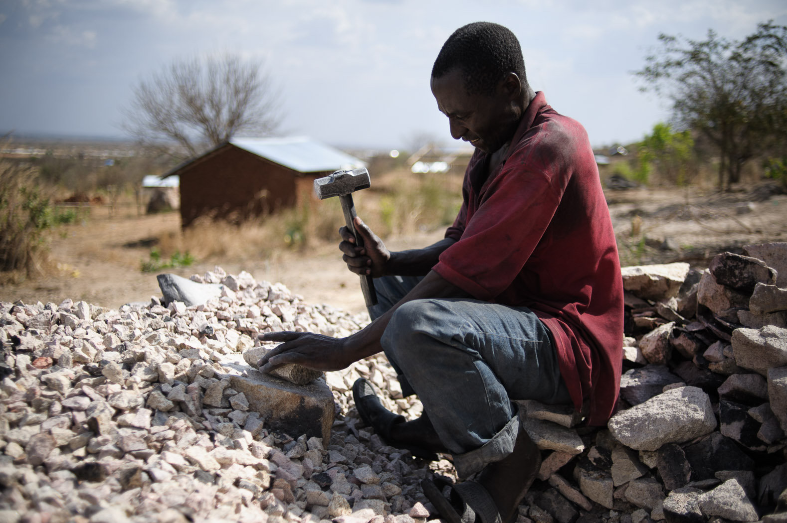 """The region holds hope of opportunities for people from more developed, neighbouring countries.  This man came from neighbouring Kenya, hoping to find a better life in South Sudan. Whilst he had hoped for a better job than breaking rocks at the base of the """"jebel"""" (mountain) at the edge of Juba, it still affords a better wage than he says he could get in his rural homeland."""