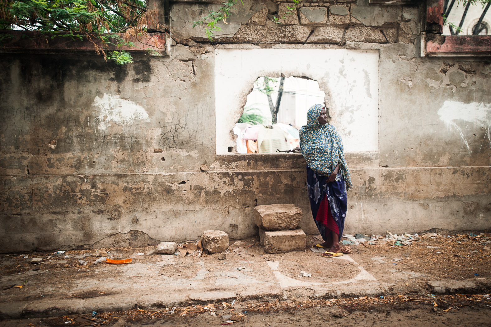 Following the drought of 2011, Mogadishu became host for thousands of internally displaced persons. Visible through the hole in this wall is one such camp, captured in May 2011.