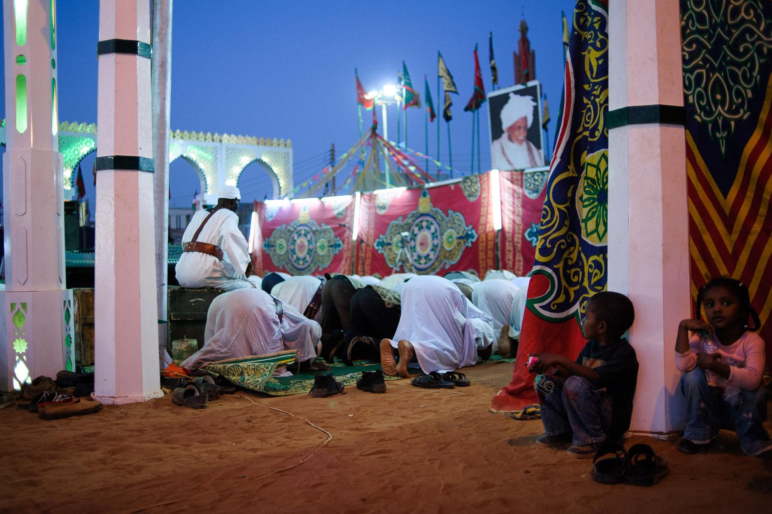 Children sit as men pray during Mawlid celebrations in Sudan.