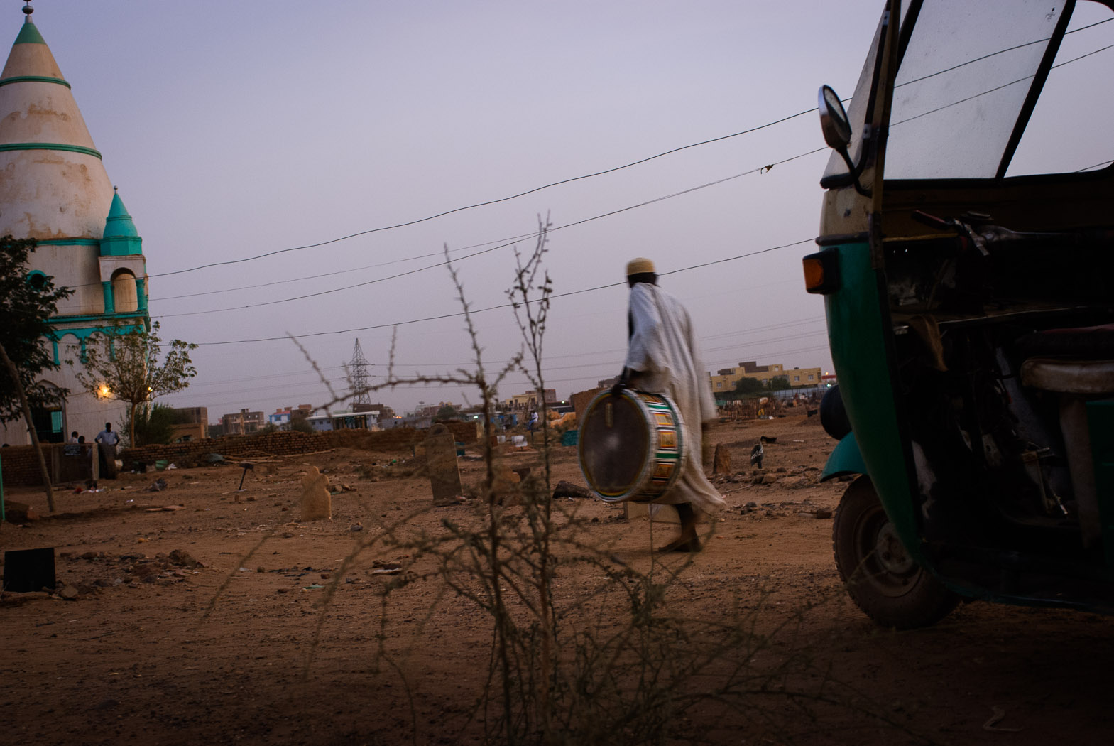 A Sudanese sufi walks with a drum to the Hamid el-Nil mosque in Omdurman.