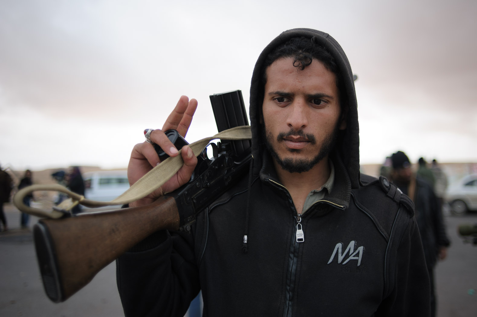 A fighter carries his gun, wearing a hooded sweater.