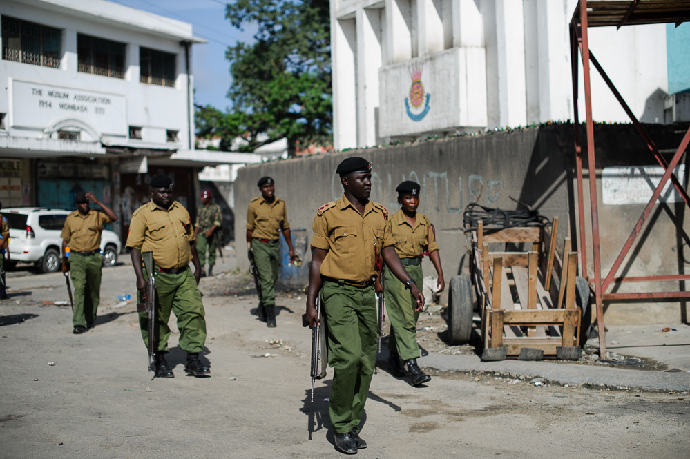 Kenyan security officers walk through the streets of the Majengo neighbourhood during rioting