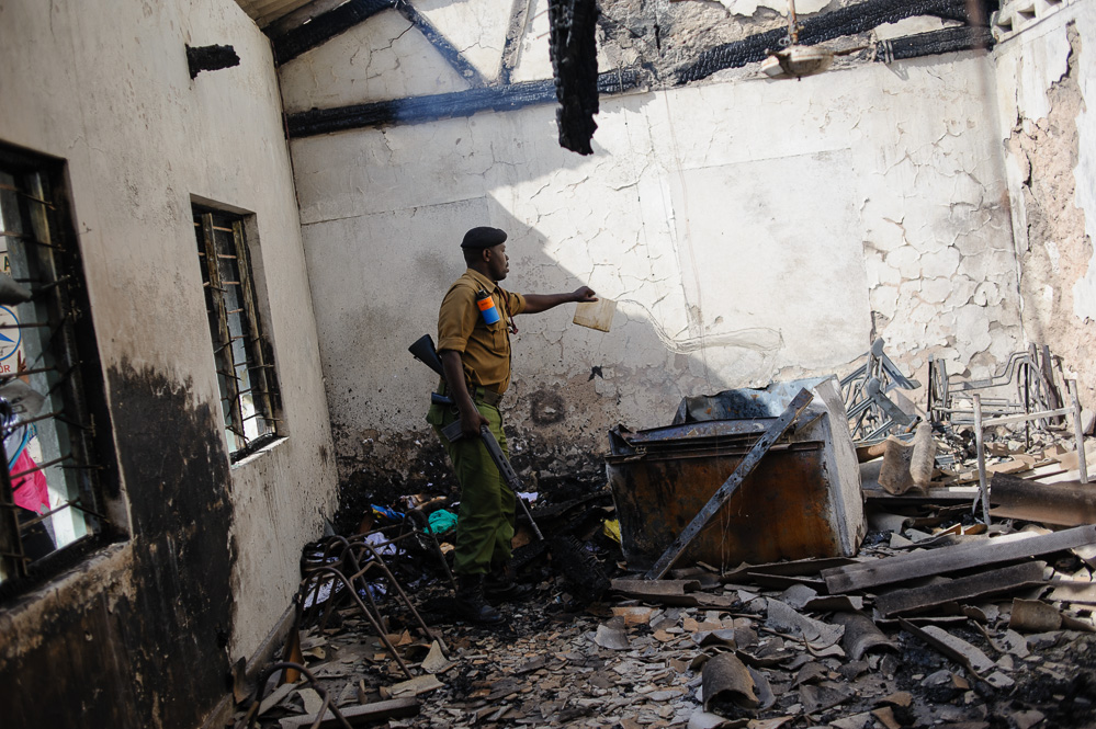 A Kenyan security officer pours water on the smouldering remnants of a church office, burned in riots following the killing of Sheikh Ibrahim