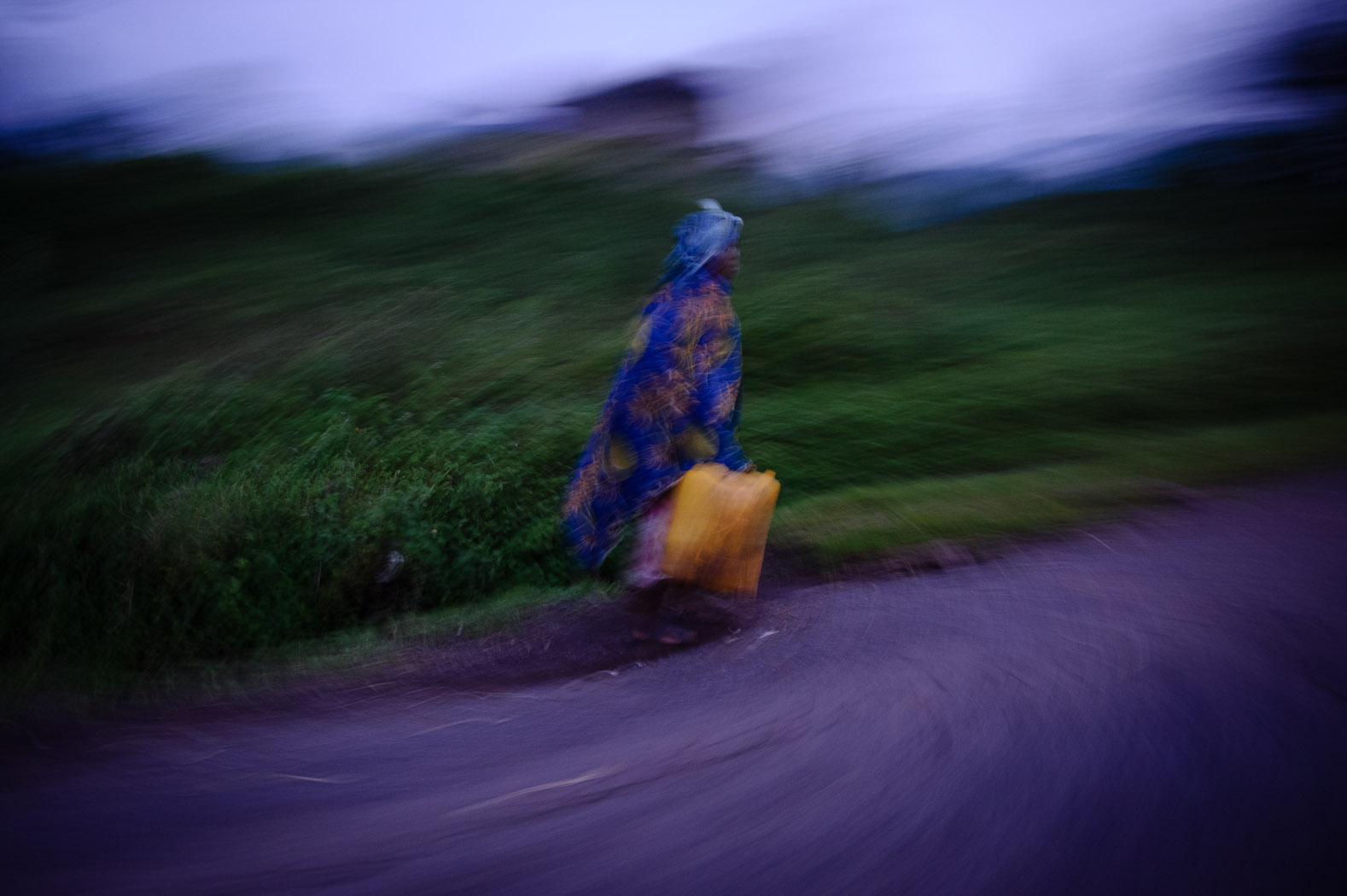 A lady carries jerry-cans of water towards an IDP settlement outside of Goma