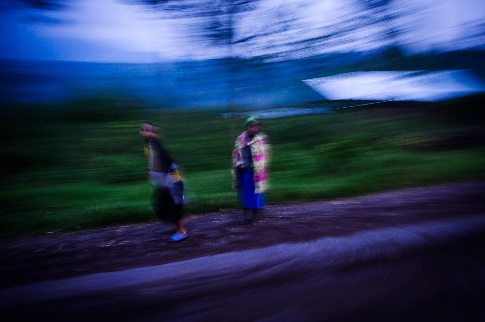 Two girls walk through Kanyarucinya