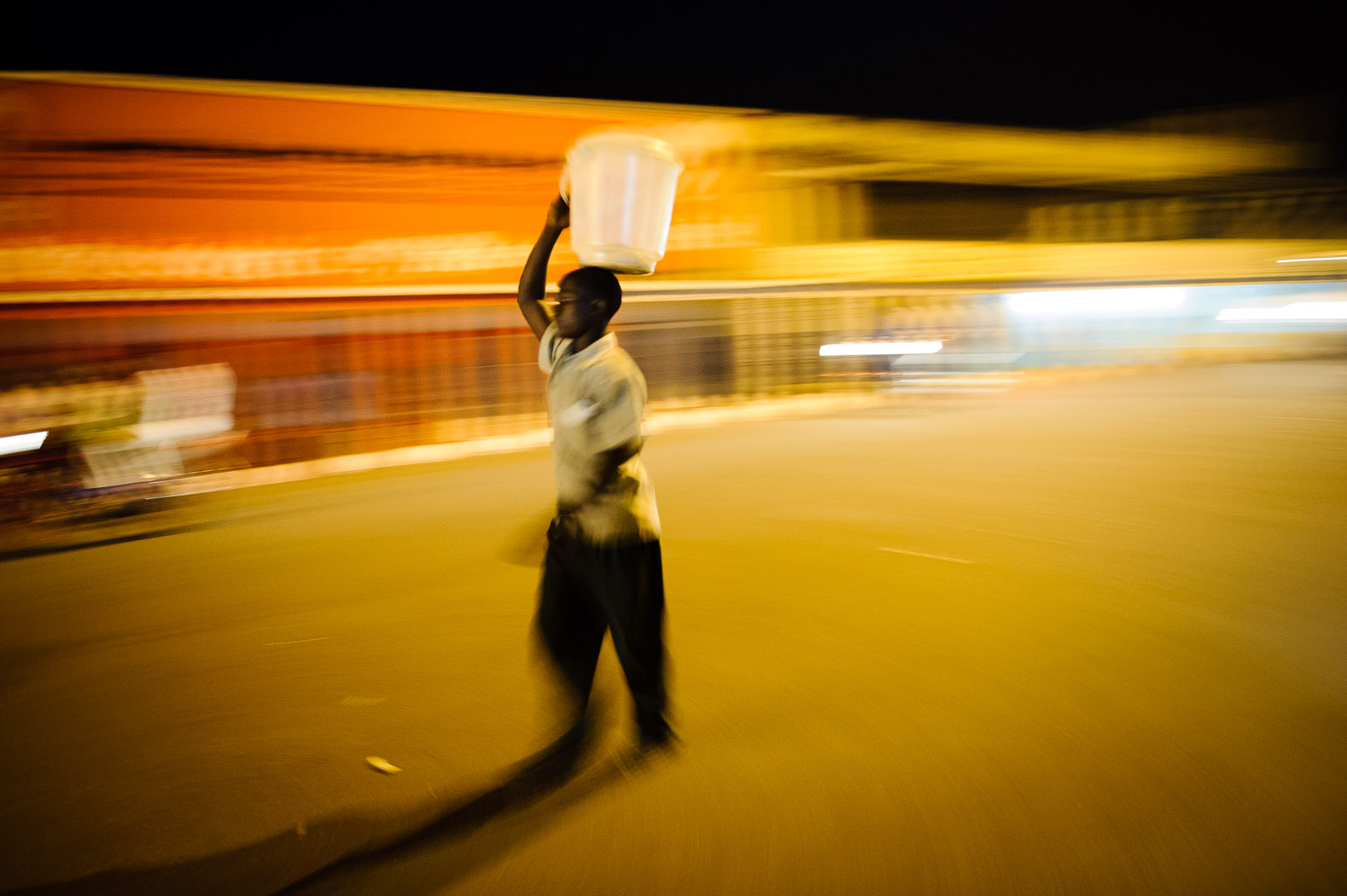 A boy carries an empty bucket used to sell food after a day of working the streets in Goma