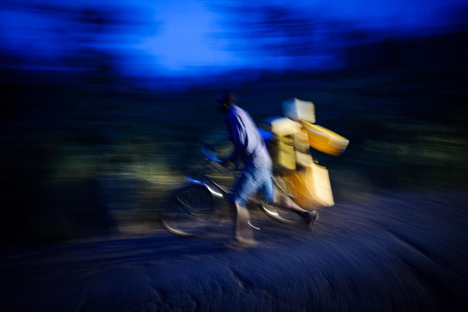 A man pushes a bicycle loaded with jerry-cans on the outskirts of Goma