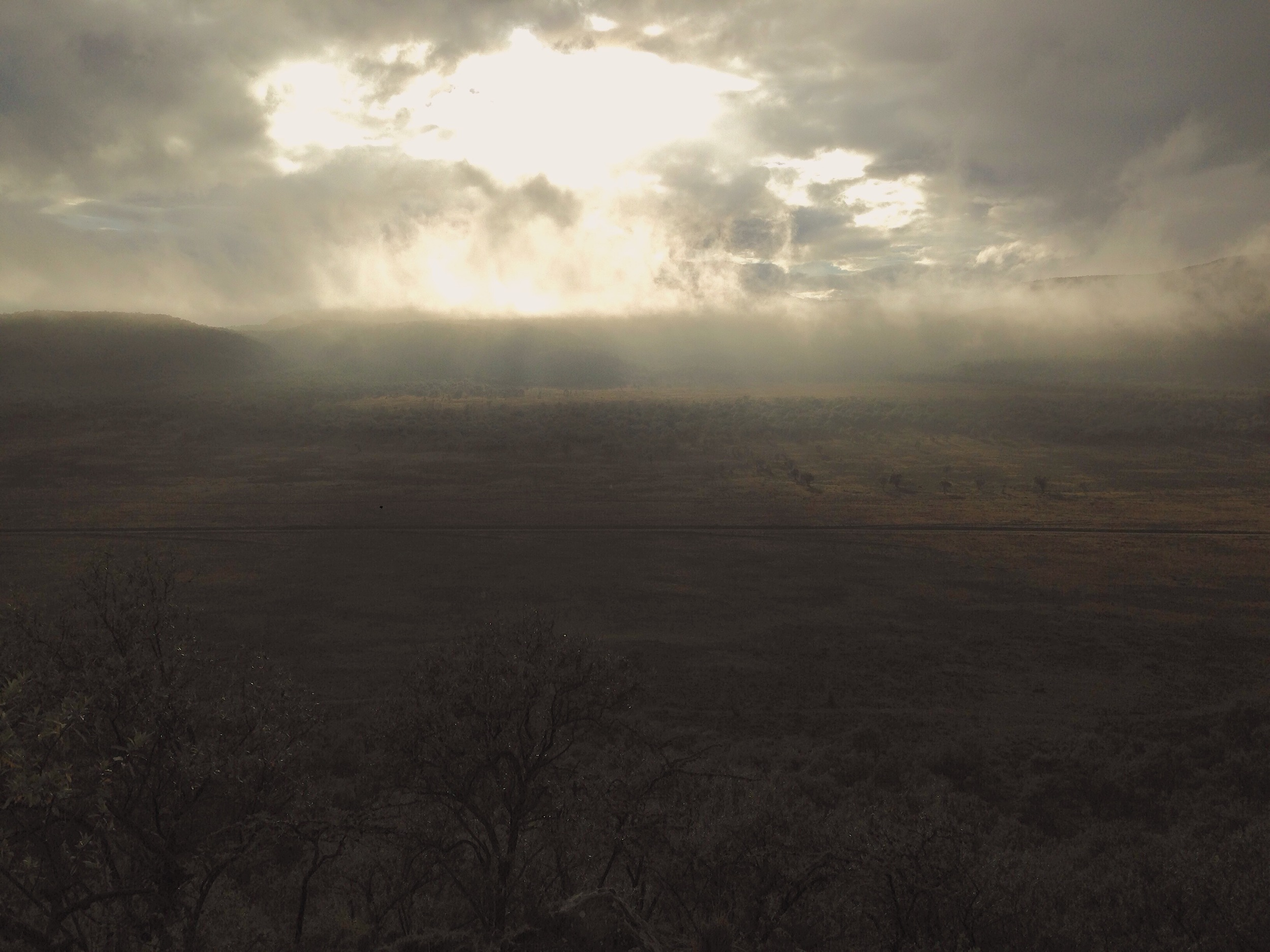 The early morning sun breaks through the clouds over the plains of Hell's Gate National Park