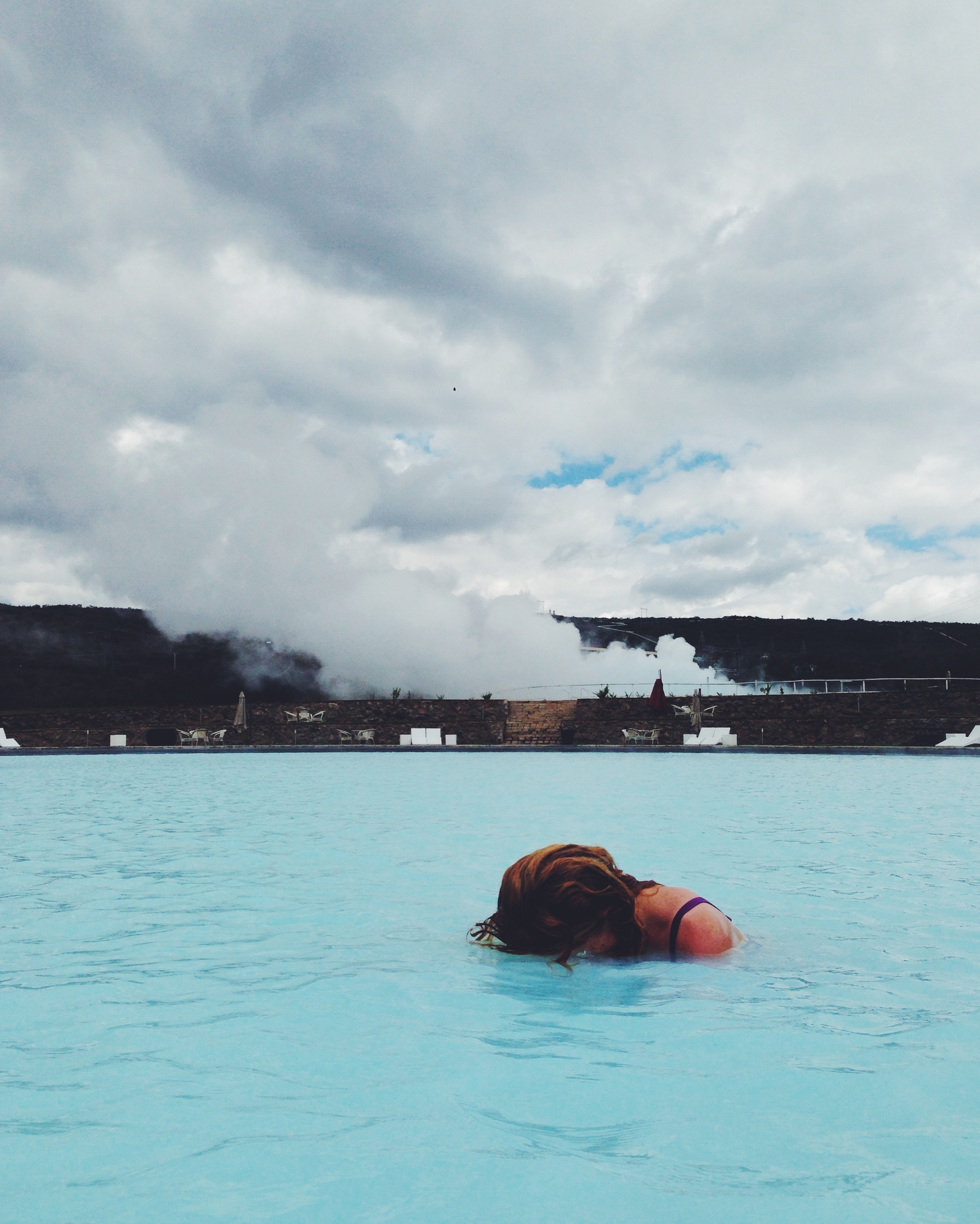 The geothermal spa with one of the cooling lagoons steaming, behind.