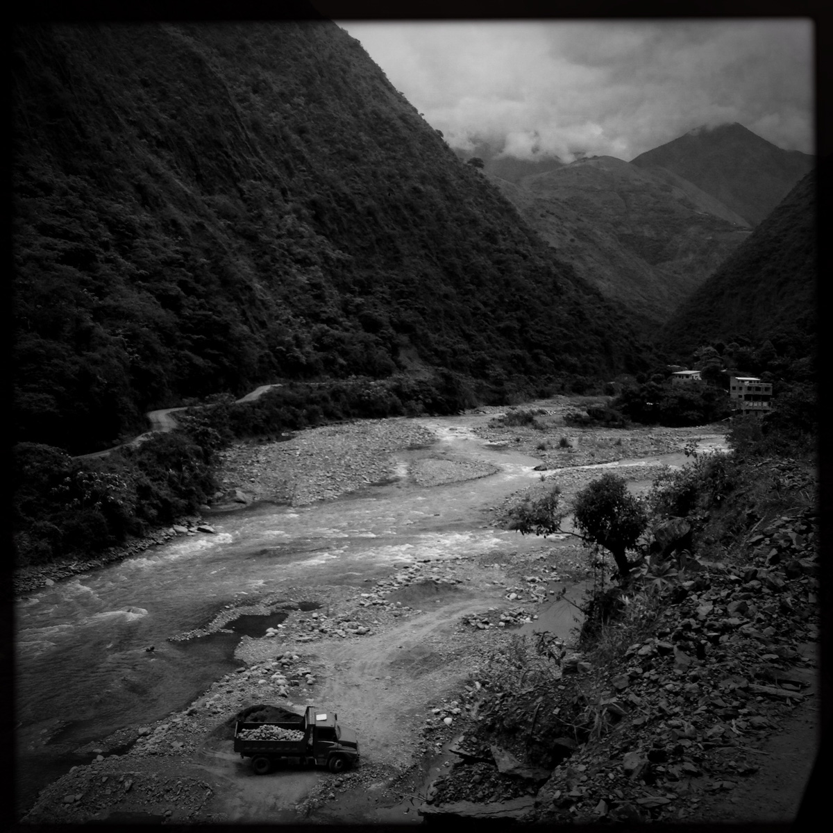 A truck loads gravel from a river bed running through a steep sided valley in *Los Yungas*, used to rebuild a road