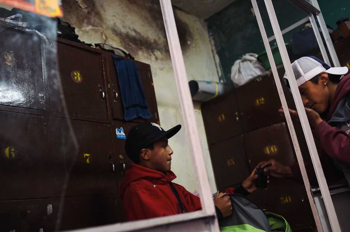 "Ruben Flores (13) (left) prepares his bag with his friend, Roberto (15) (right), in the locker-room of the ""New Day Foundation"" association in La Paz, Bolivia. Ruben is a shoe-shiner and helps support his family through the wages he earns."