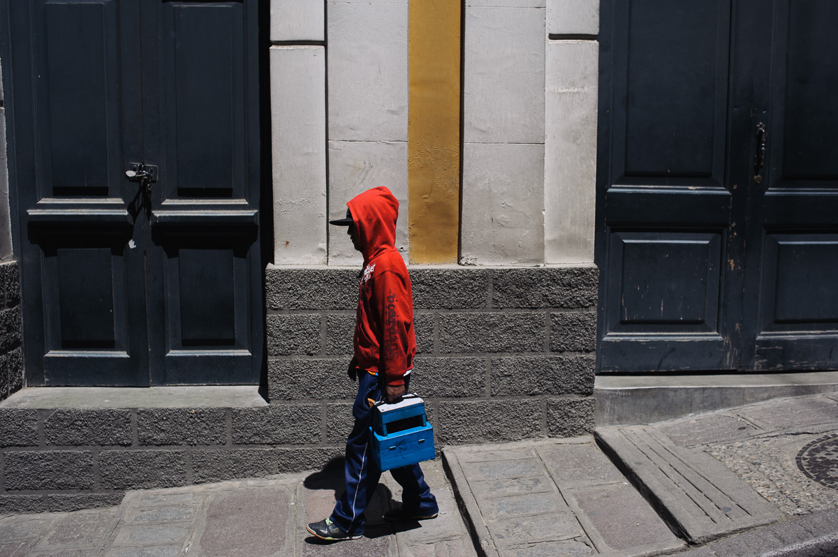 Ruben Flores (13) walks the streets of La Paz, Bolivia, with his shoe-shining box and stool, in search of clients.
