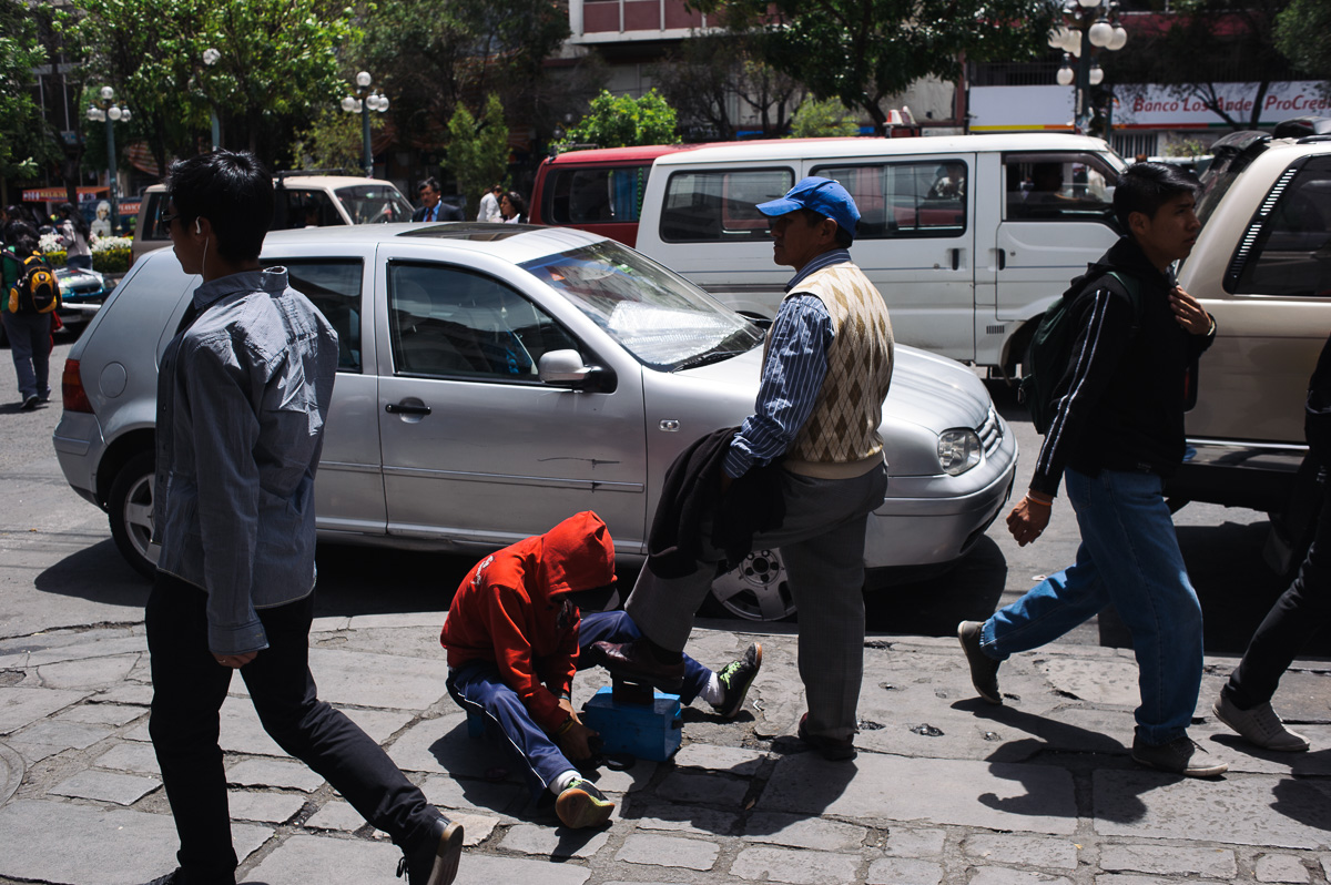 Ruben Flores (13) shines the shoe of a man in the street of central La Paz, Bolivia, as pedestrians walk past.
