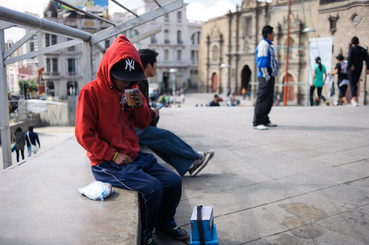 Ruben Flores (13) drinks a cup of tea given to him by a women's organisation, whilst he works as a shoe shiner on the streets of La Paz, Bolivia.